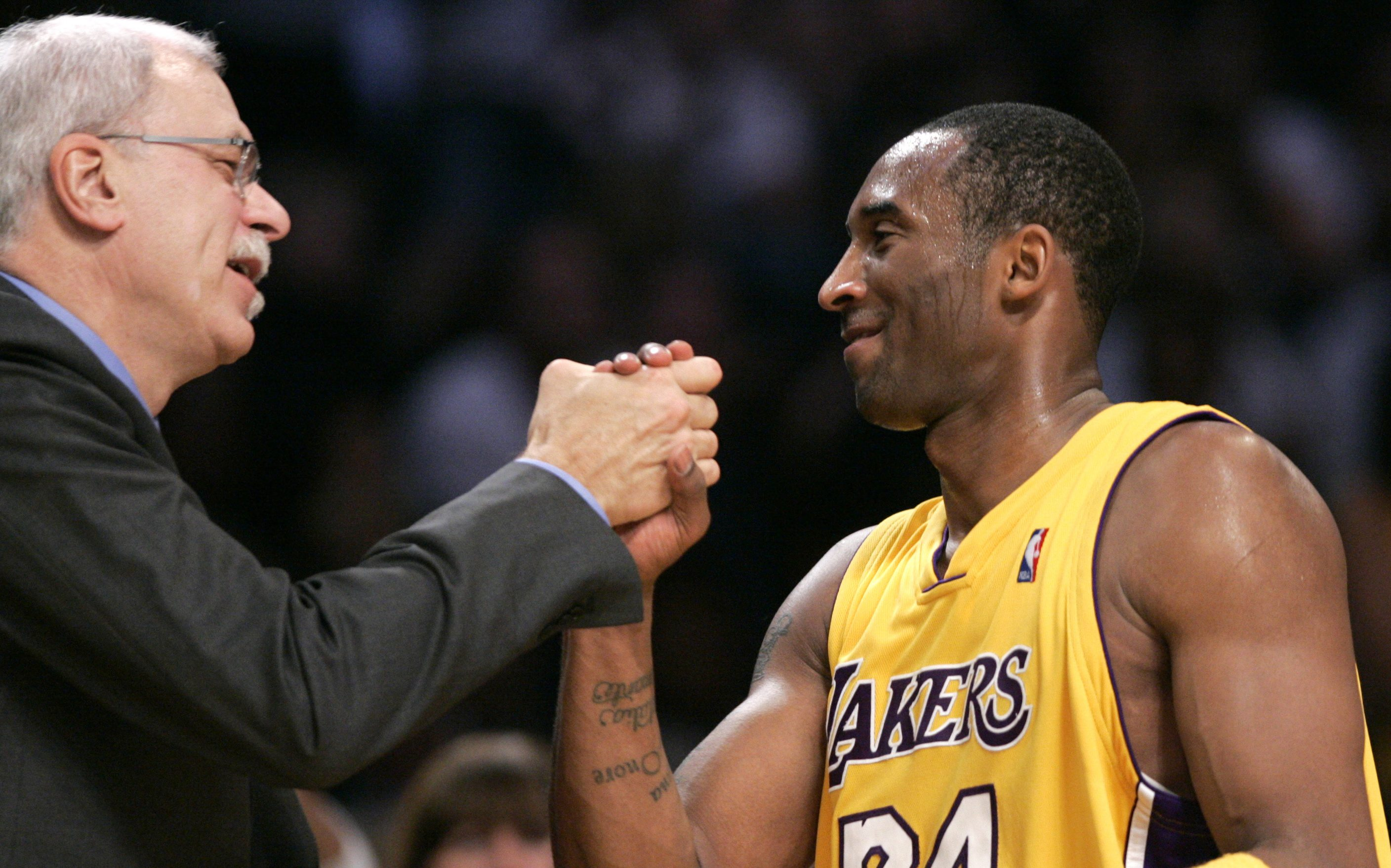 Los Angeles Lakers' Kobe Bryant (R) is congratulated by coach Phil Jackson after leaving their NBA game against the Utah Jazz having scored 52 points, in Los Angeles