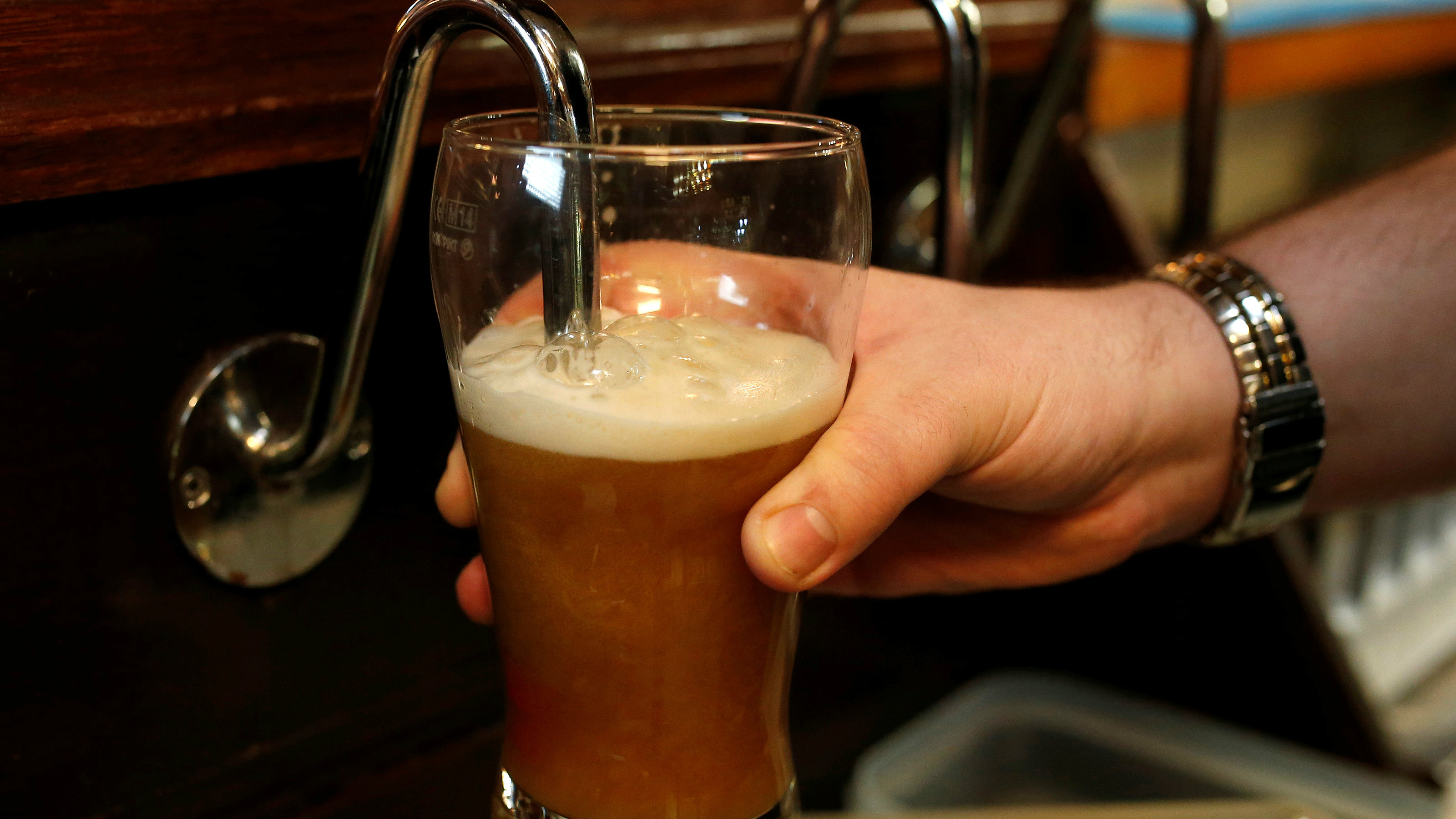 A barman pulls a pint of beer in a pub in Liverpool northern England