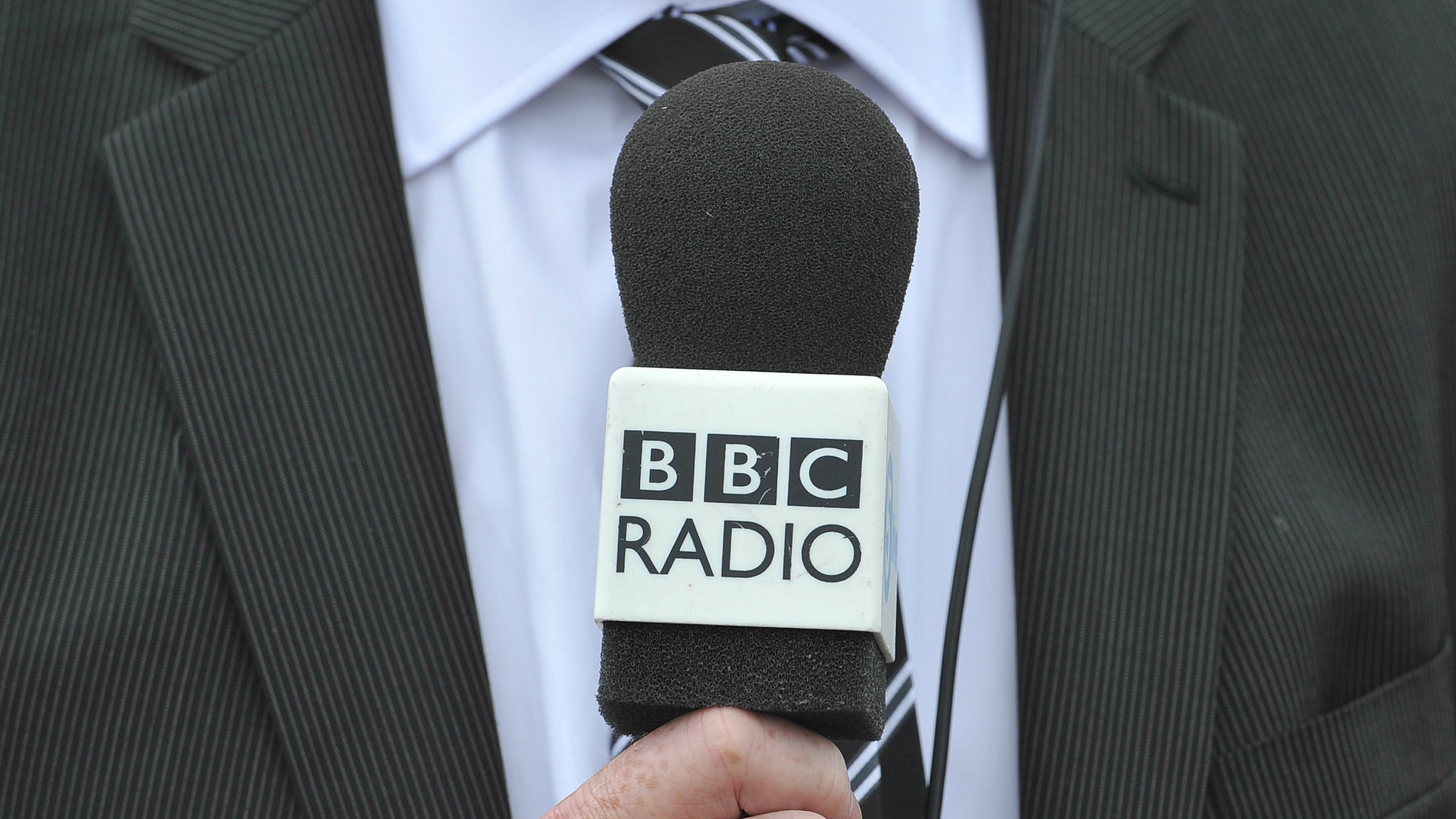 A man holds a BBC radio microphone as he is interviewed at Heathrow airport in west London May 12, 2011.