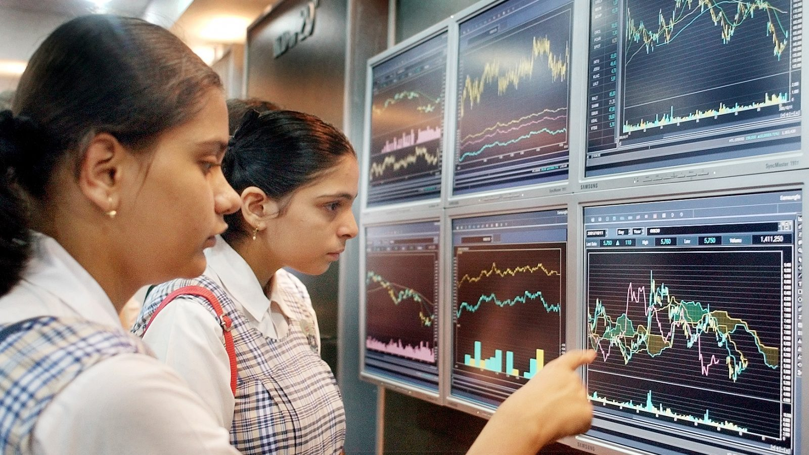 "Indian schoolgirls visiting a newly opened digital technology centre look at stock market graphs displayed on plasma screens in Bombay March 5, 2003. The ""Digital Adventure"" technology centre, set up by South Korean technology giant Samsung, sees hundreds of school children visiting daily. India, with its vast army of software professionals, is seeking to become a global software powerhouse. REUTERS/Sherwin Crasto  SC/JD - RTR12JCA"