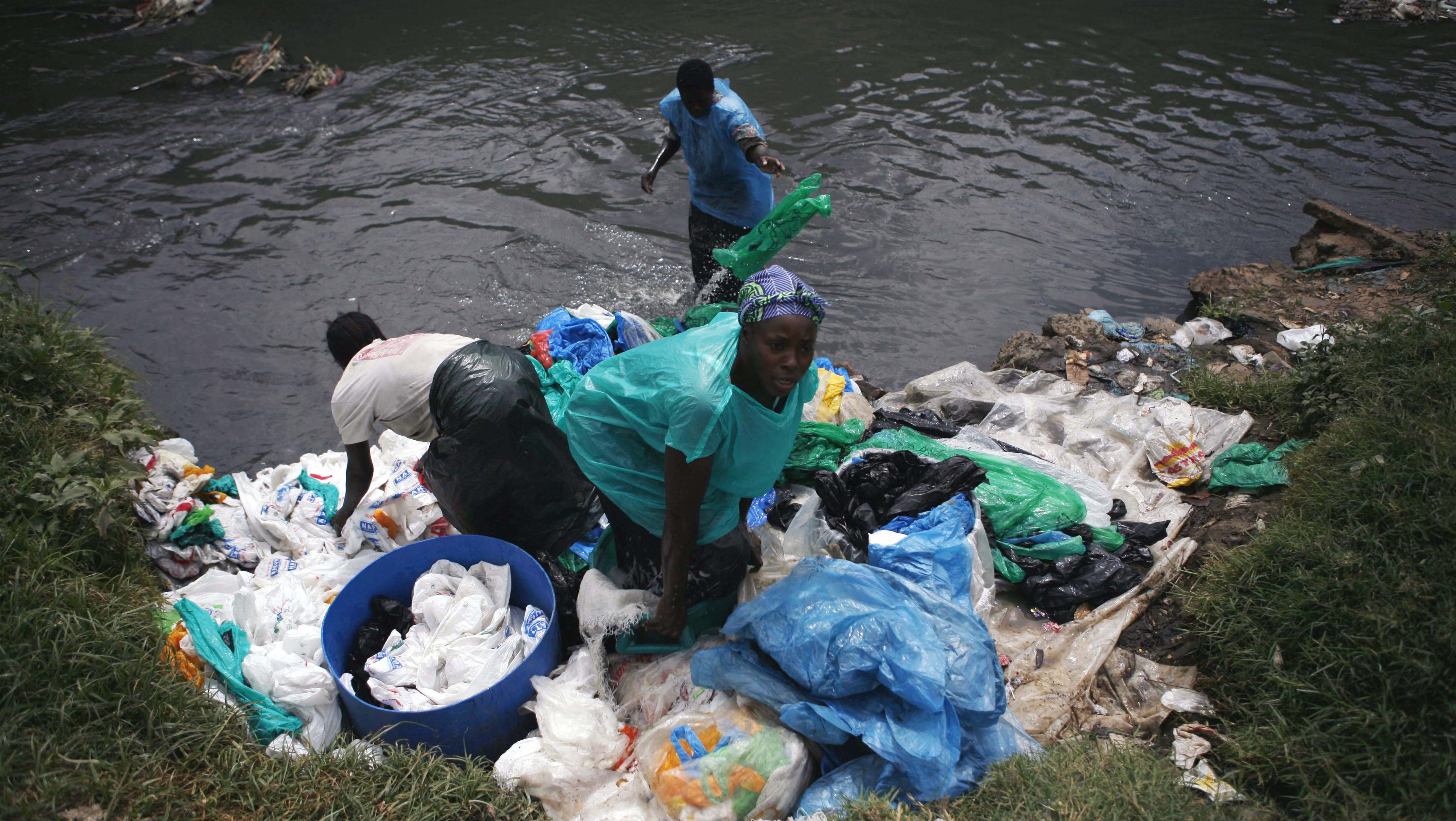 Women wash garbage and plastic bags collected from Dandora rubbish dump in Nairobi