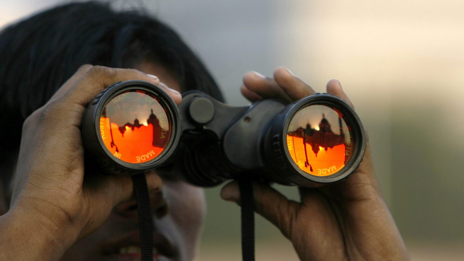 A visitor views the Taj Mahal hotel, which is reflected in his binoculars, in Mumbai December 10, 2008. REUTERS/Arko Datta (INDIA) - RTR22GDD