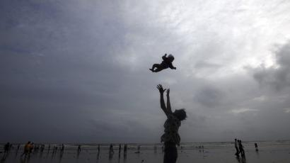 man playing with baby on beach