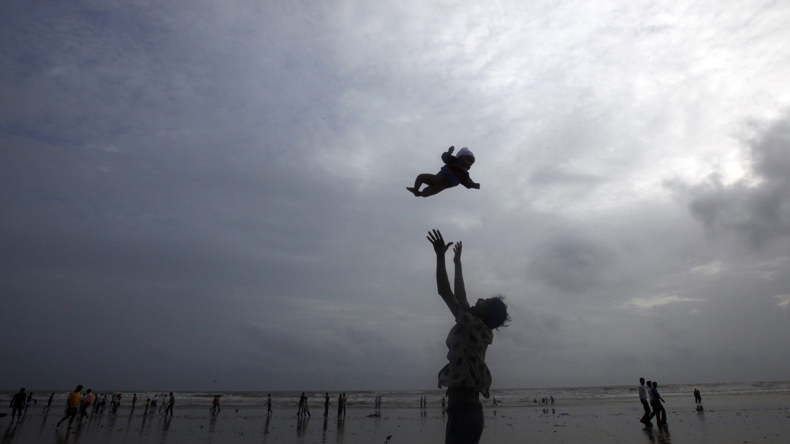 A man plays with his child against the backdrop of monsoon clouds on a beach in Mumbai July 23, 2010.