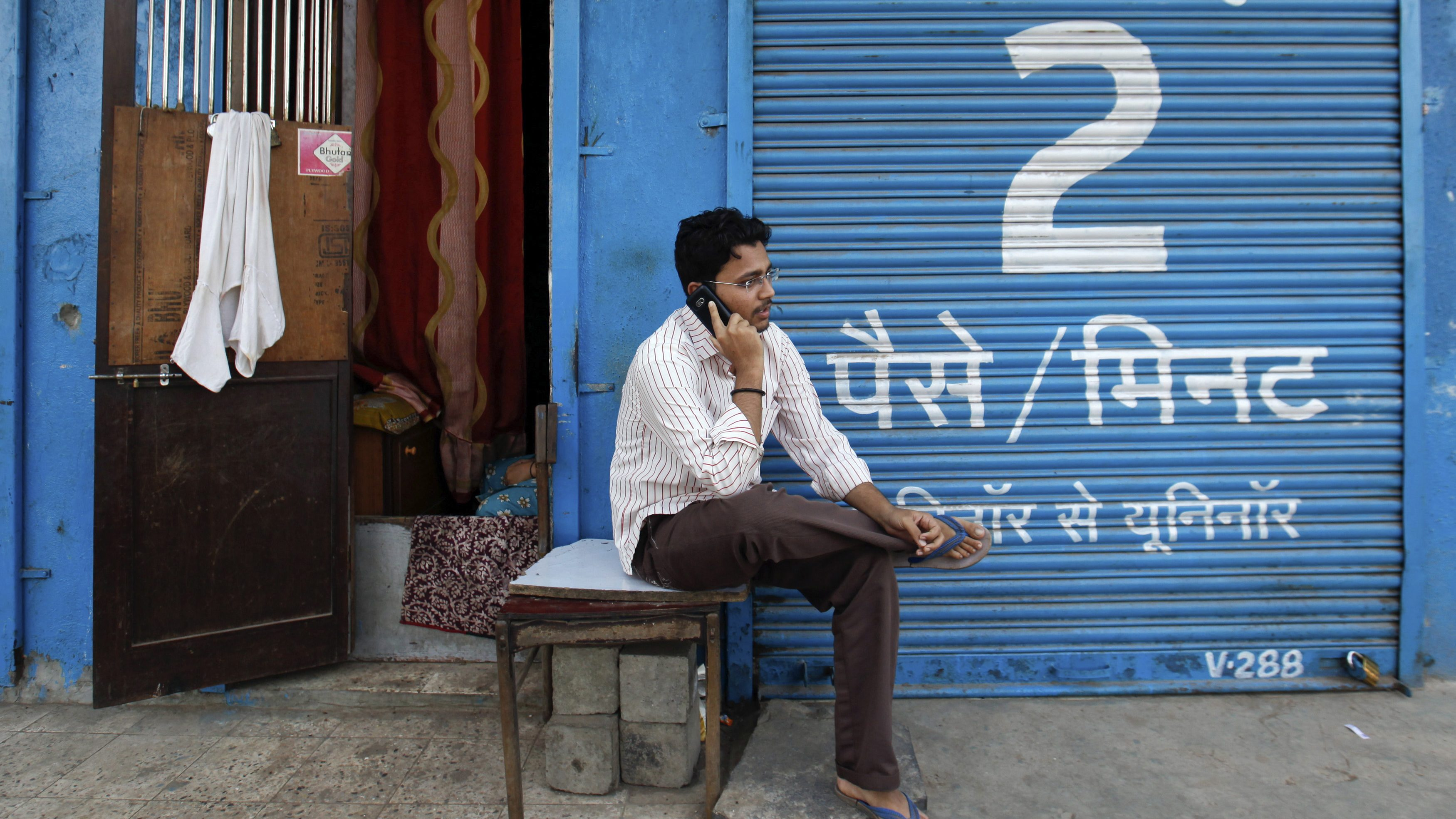 A man speaks on a mobile phone in front of a closed shop displaying an advertisement for Uninor on its shutters in Mumbai February 6, 2012. Norway's Telenor ASA plans to fight an order by India's Supreme Court to cancel 22 telecoms licences held by its Indian joint venture, but has not ruled out abandoning the country altogether, the head of the company's Asian operations said. Telenor's joint venture with Unitech, which operates under the Uninor brand, has been among the most aggressive of India's newer telecoms companies.