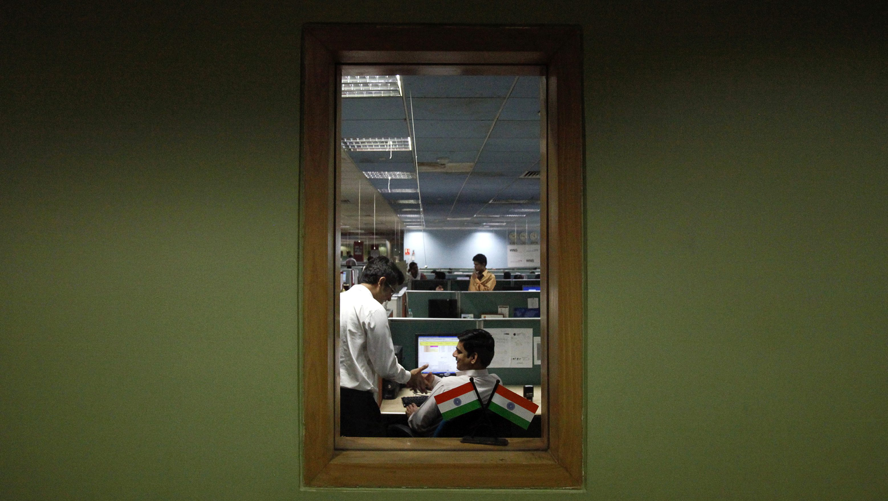 Employees are pictured through a window as they work on the floor of the outsourcing company WNS in Mumbai March 19, 2012. Indian back-office company WNS Holdings Ltd may launch the first of three customer-service centres in the United States over the next quarter, its CEO Keshav Murugesh said, as it looks to boost revenues in its second largest market. REUTERS/Vivek Prakash (INDIA - Tags: BUSINESS EMPLOYMENT) - RTR2ZKTH