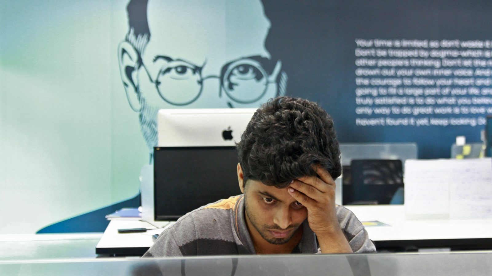 An employee works on a computer terminal against the backdrop of a picture of late Apple co-founder Steve Jobs at the Start-up Village in Kinfra High Tech Park in the southern Indian city of Kochi October 13, 2012. Three decades after Infosys, India's second-largest software service provider, was founded by middle-class engineers, the country has failed to create an enabling environment for first-generation entrepreneurs. Startup Village wants to break the logjam by helping engineers develop 1,000 Internet and mobile companies in the next 10 years. It provides its members with office space, guidance and a chance to hobnob with the stars of the tech industry. But critics say this may not even be the beginning of a game-changer unless India deals with a host of other impediments - from red tape to a lack of innovation and a dearth of investors - that are blocking entrepreneurship in Asia's third-largest economy. To match Feature INDIA-TECHVILLAGE/ Picture taken October 13, 2012. REUTERS/Sivaram V (INDIA - Tags: BUSINESS SCIENCE TECHNOLOGY EMPLOYMENT TPX IMAGES OF THE DAY) - RTR3B6DX