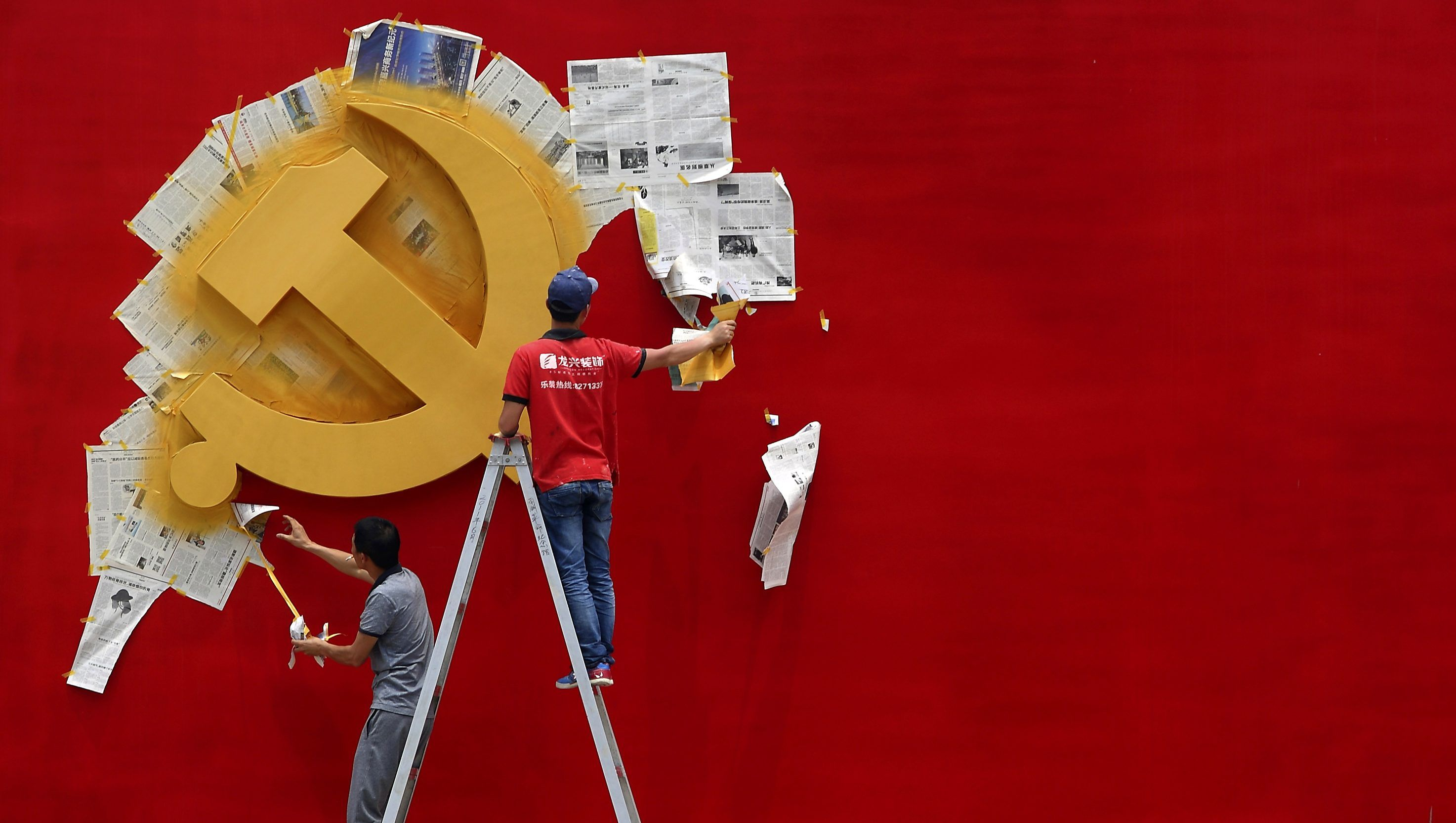 Workers peel papers off a wall as they re-paint the Chinese Communist Party flag on it at the Nanhu revolution memorial museum in Jiaxing, Zhejiang province May 21, 2014.