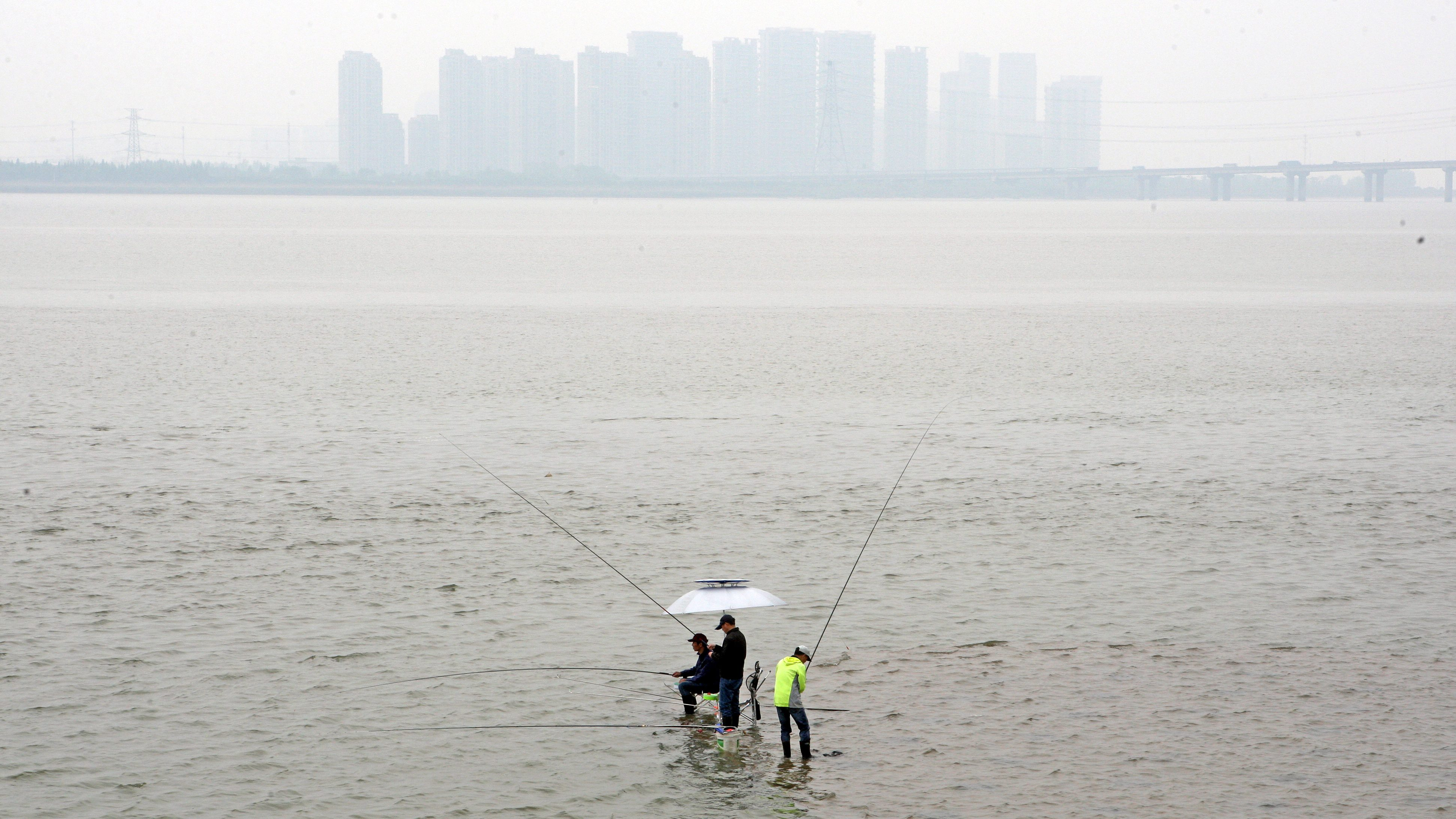 People fish on the Qiantang River in Hangzhou, Zhejiang province, China, April 21, 2017. Picture taken April 21, 2017.