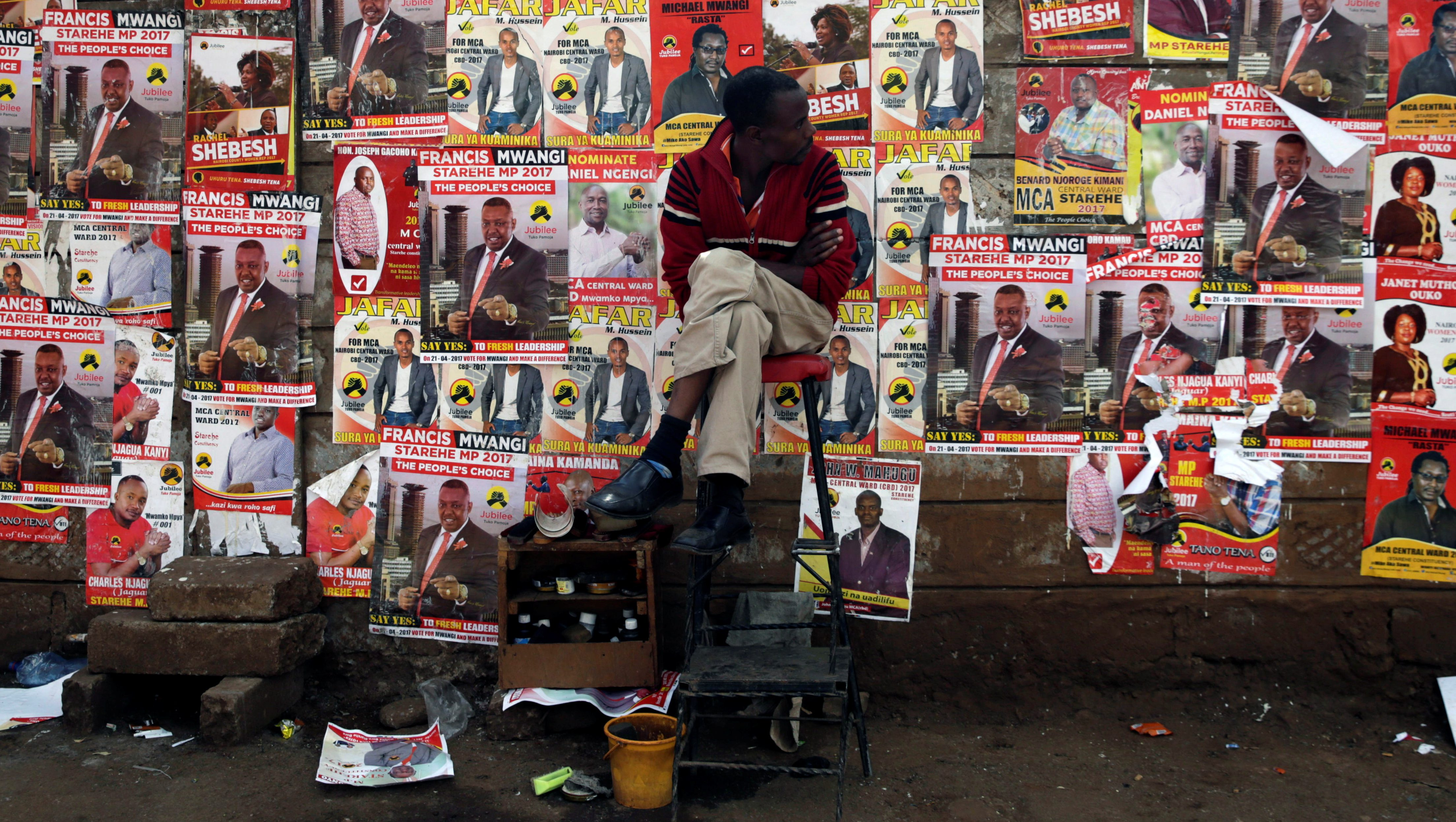 A man looks at campaign posters as he waits to cast his ballot, during the Jubilee Party primary elections, outside a polling centre in Nairobi, Kenya April 26, 2017.