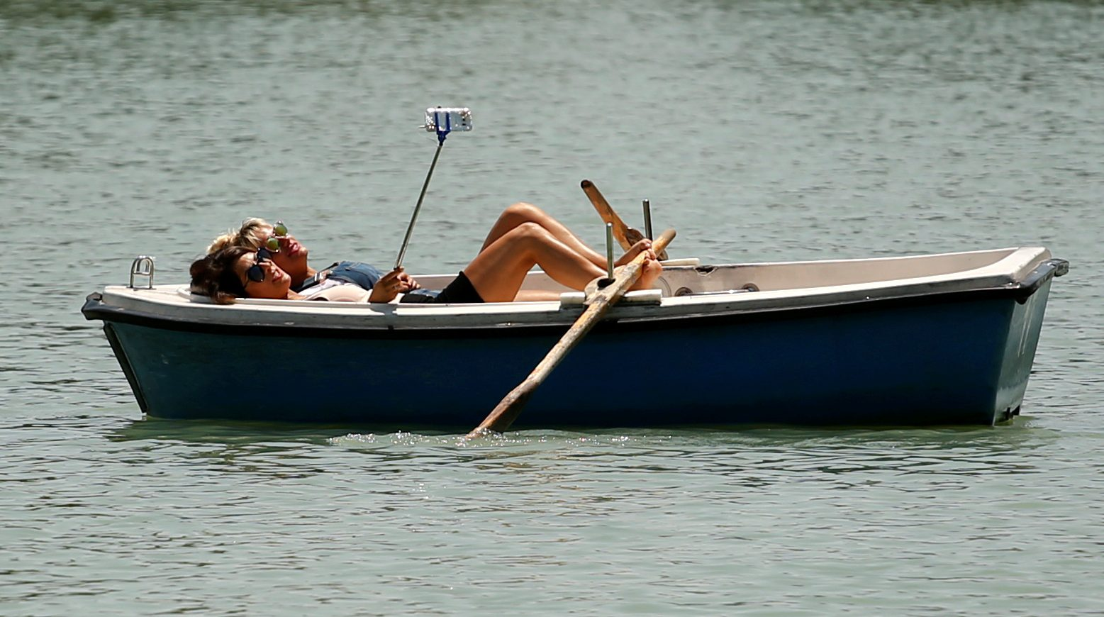 Two woman take a selfie on a boat during the unusual high temperatures at Retiro park in Madrid, Spain