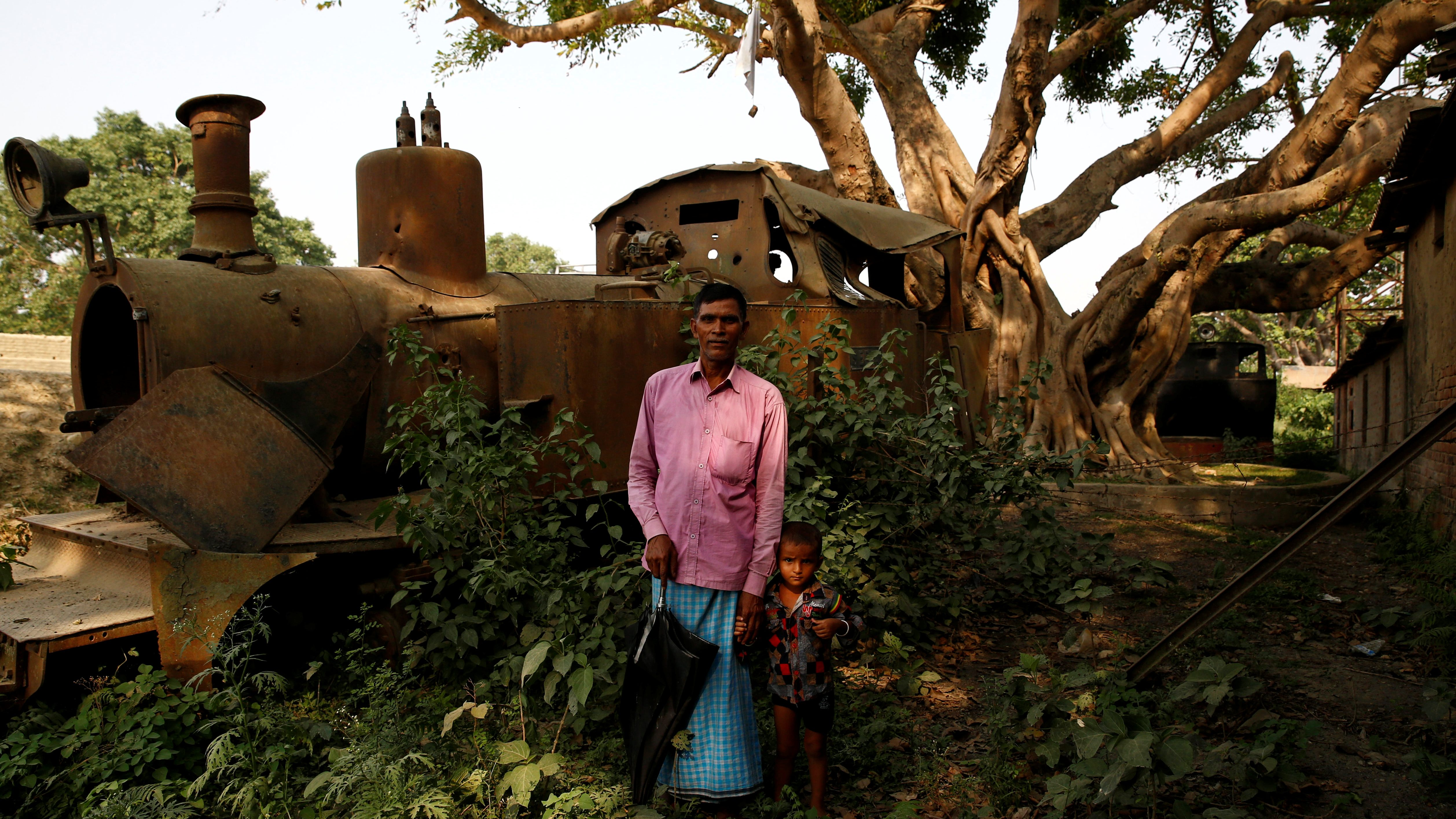 Train driver Rafid Kabadi, 49, with his grandson in front of an abandoned train he used to drive, in Janakpur, Nepal.
