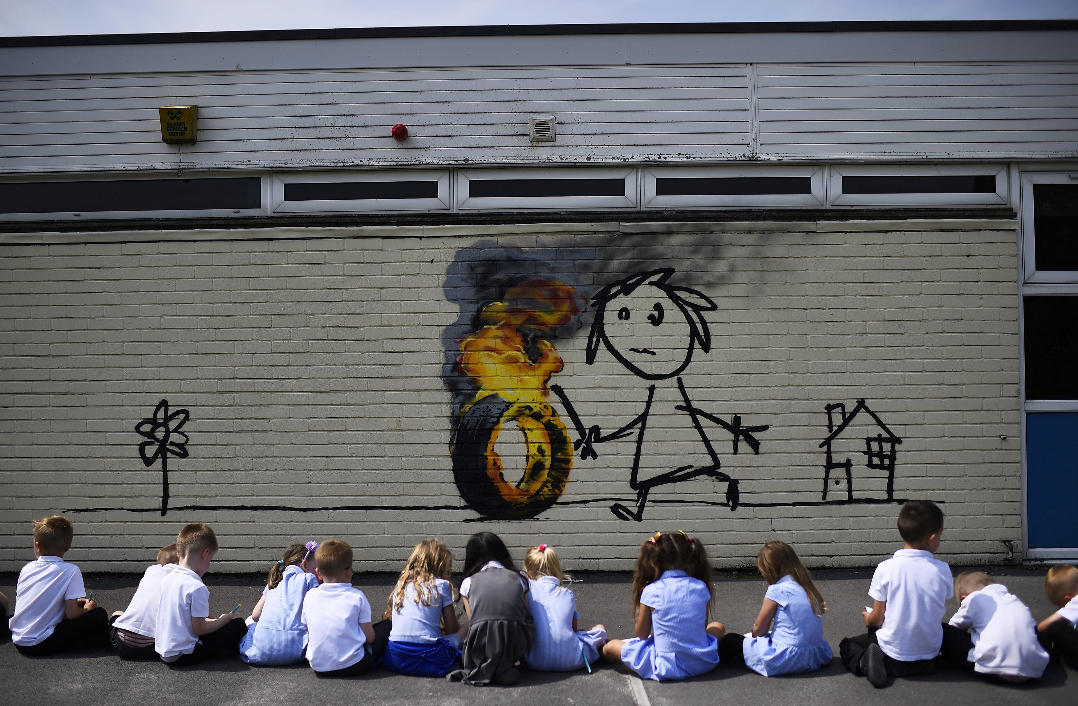 Reception class school children sit in a row as they draw a mural, attributed to graffiti artist Banksy, painted on the outside of a class room at the Bridge Farm Primary School in Bristol, Britain June 6, 2016.