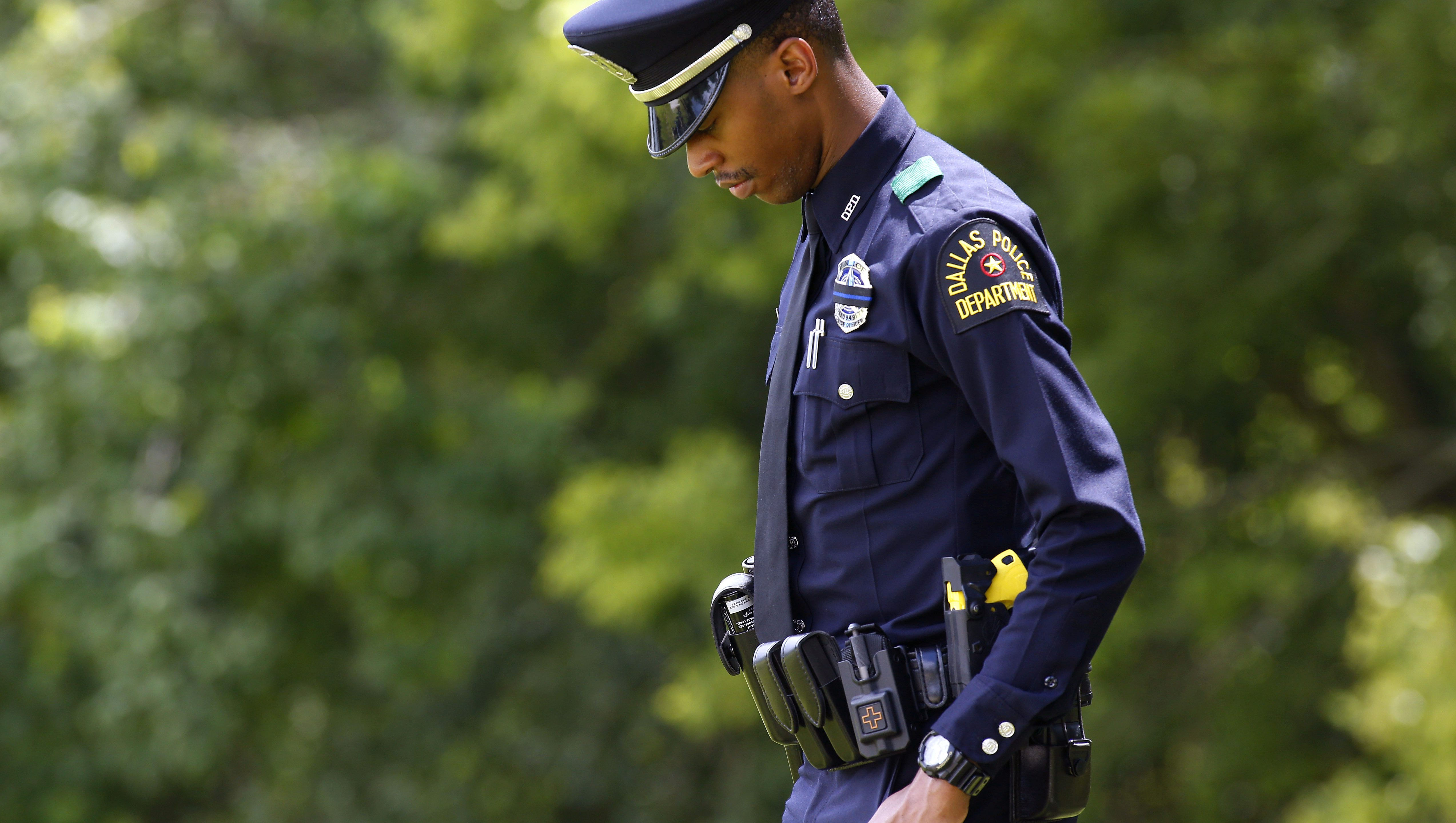 A Dallas police officer makes his way to funeral services for Baton Rouge Police Department officer Montrell Jackson at Greenoaks Memorial Park in Baton Rouge, Louisiana, U.S. July 25, 2016.  REUTERS/Jonathan Bachman - RTSJLHQ