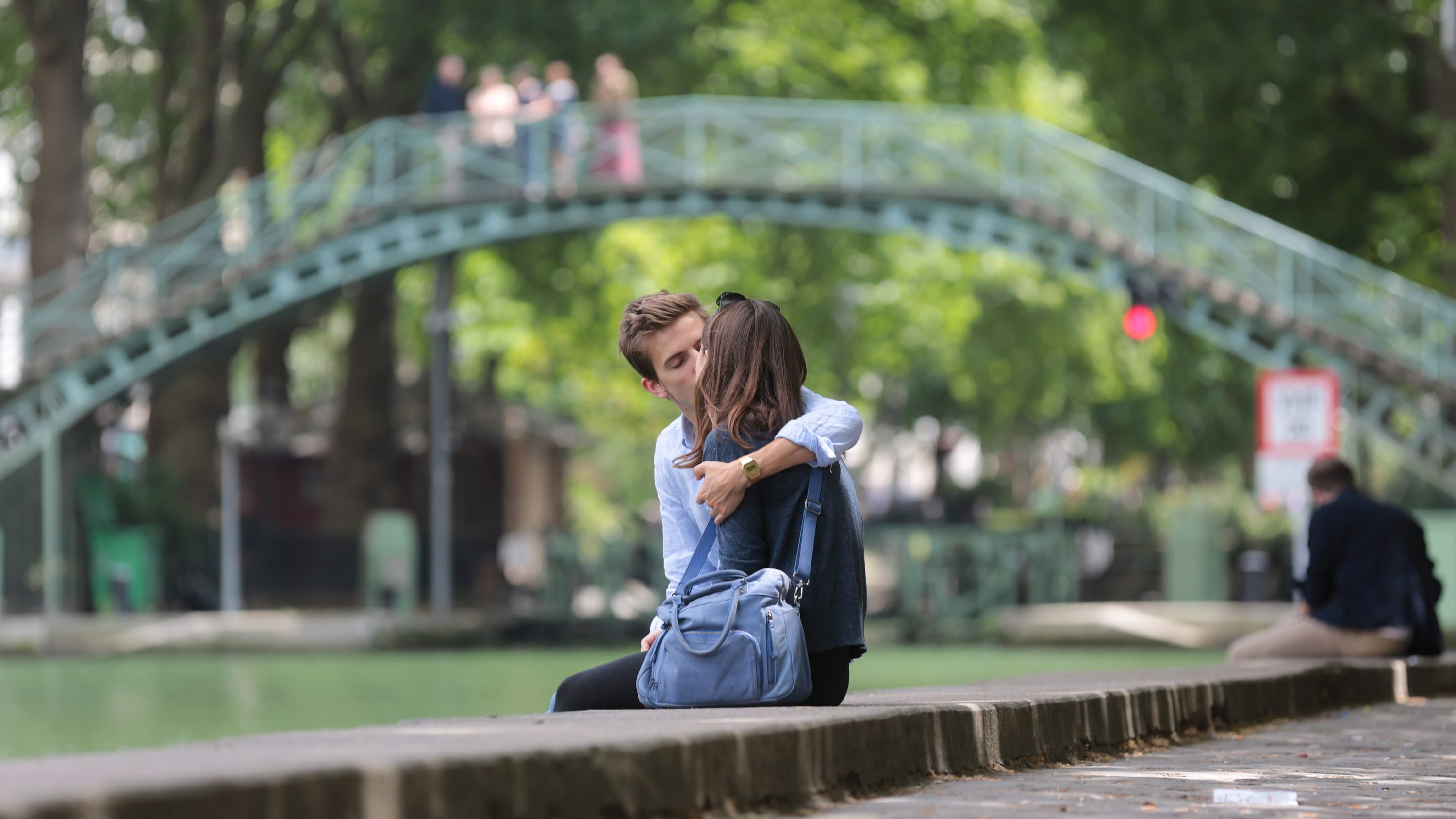 A young couple kisses while sitting on the edge of the Canal Saint-Martin in Paris, France, June 20, 2015. Inauguarated in 1825, the 4.5 km waterway comprised of nine locks running through the 10th and 11th districts of the French capital.
