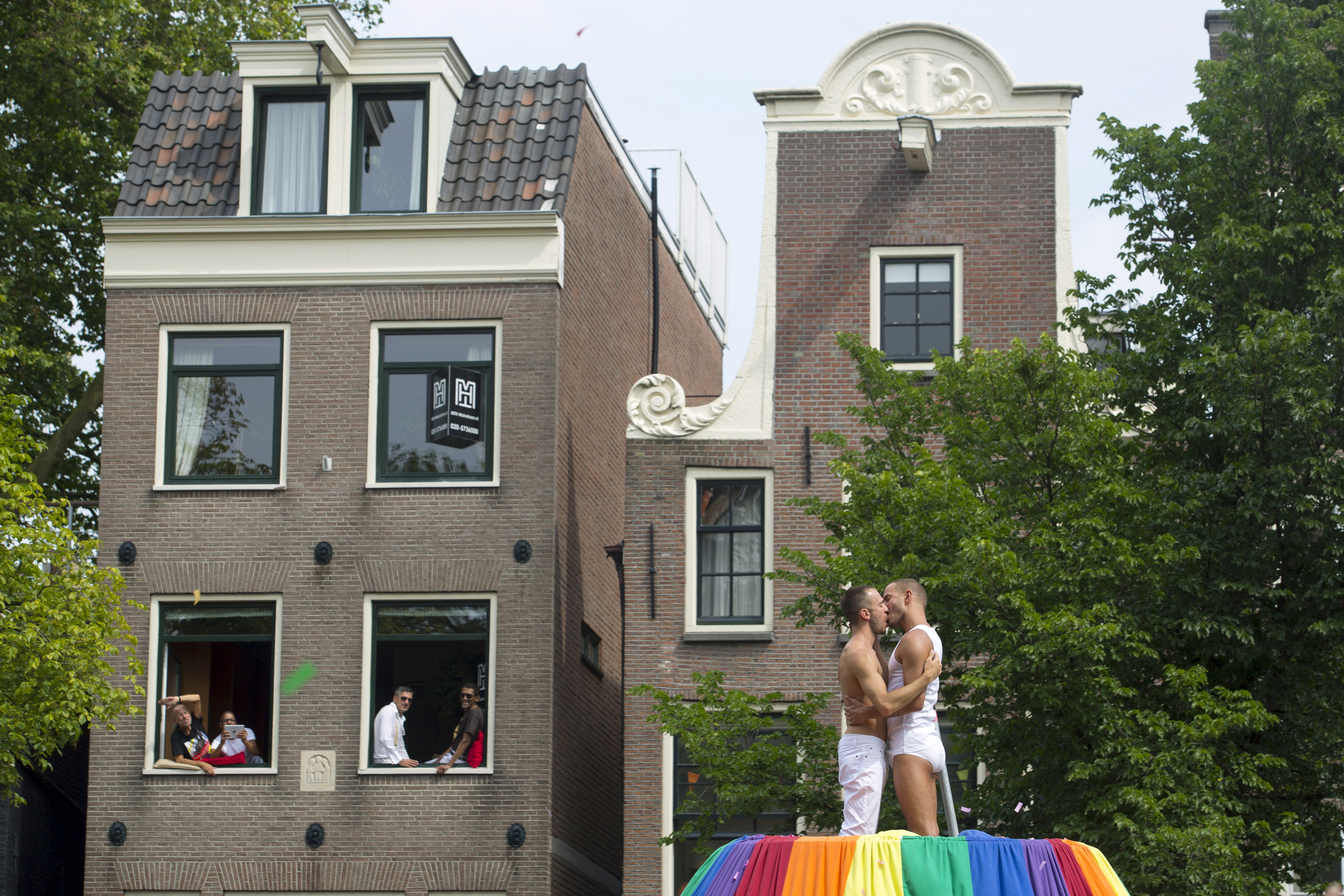 Participants of the 20th Canal Gay Parade celebrate on a boat in the Prinsengracht in Amsterdam, the Netherlands August 1, 2015.