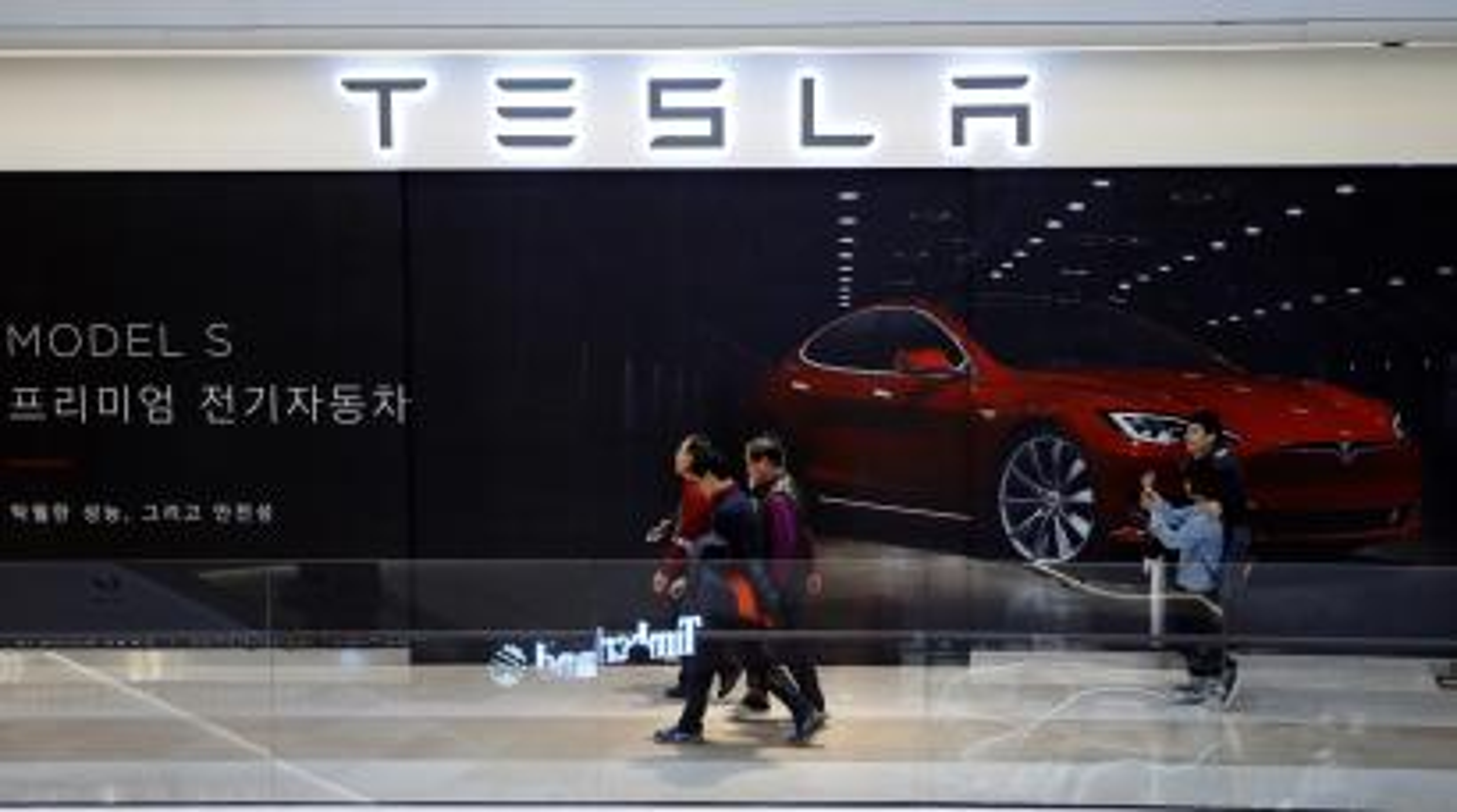 People walk past a planned store of Tesla in Hanam, South Korea, December 22, 2016.