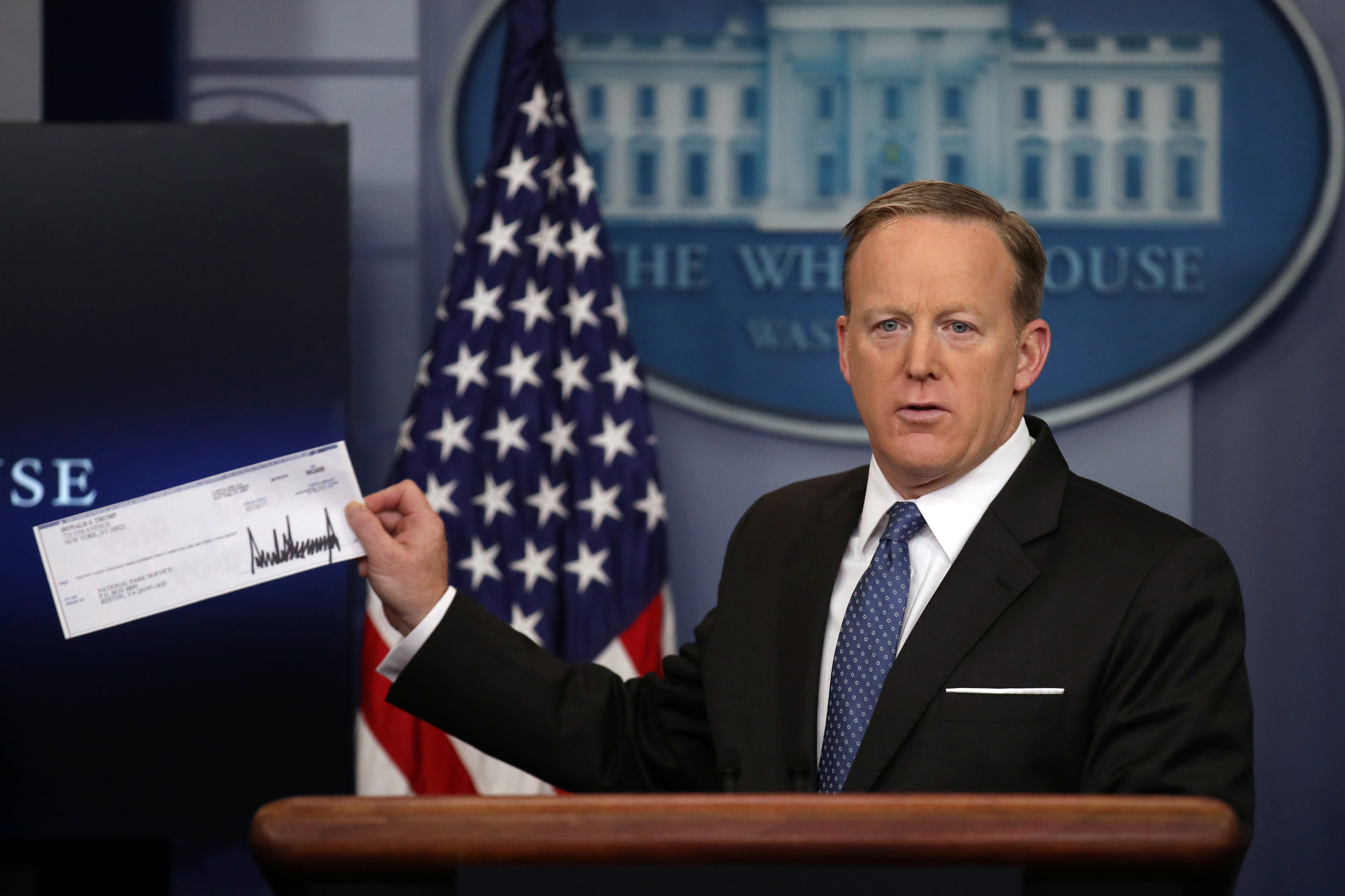 White House Press Secretary Sean Spicer shows a check from U.S. President Donald Trump's salary which will be donated to the National Park Service during a daily press briefing at the White House in Washington, U.S., April 3, 2017.