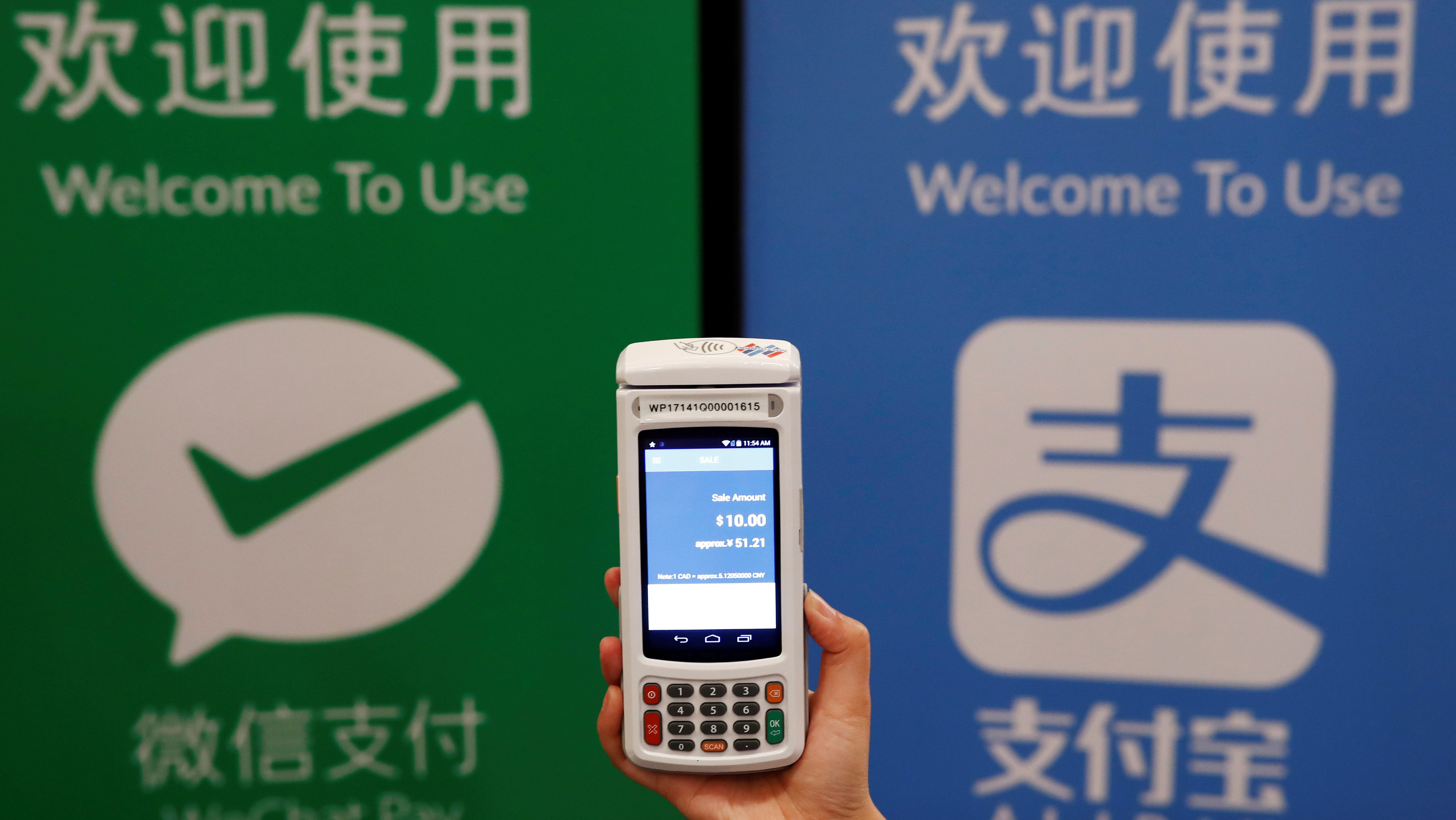 "A woman demonstrates a high security digital unit built by Motion Pay, that allows customers to pay in Chinese yuan renminbi using Chinese online money payment services ""WeChat Pay"", and ""Alipay"", where payments get converted to Canadian dollars at point of sales locations in Canadian stores and businesses, in Toronto, Canada, May 24, 2017. REUTERS/Mark Blinch - RTX37HXO"