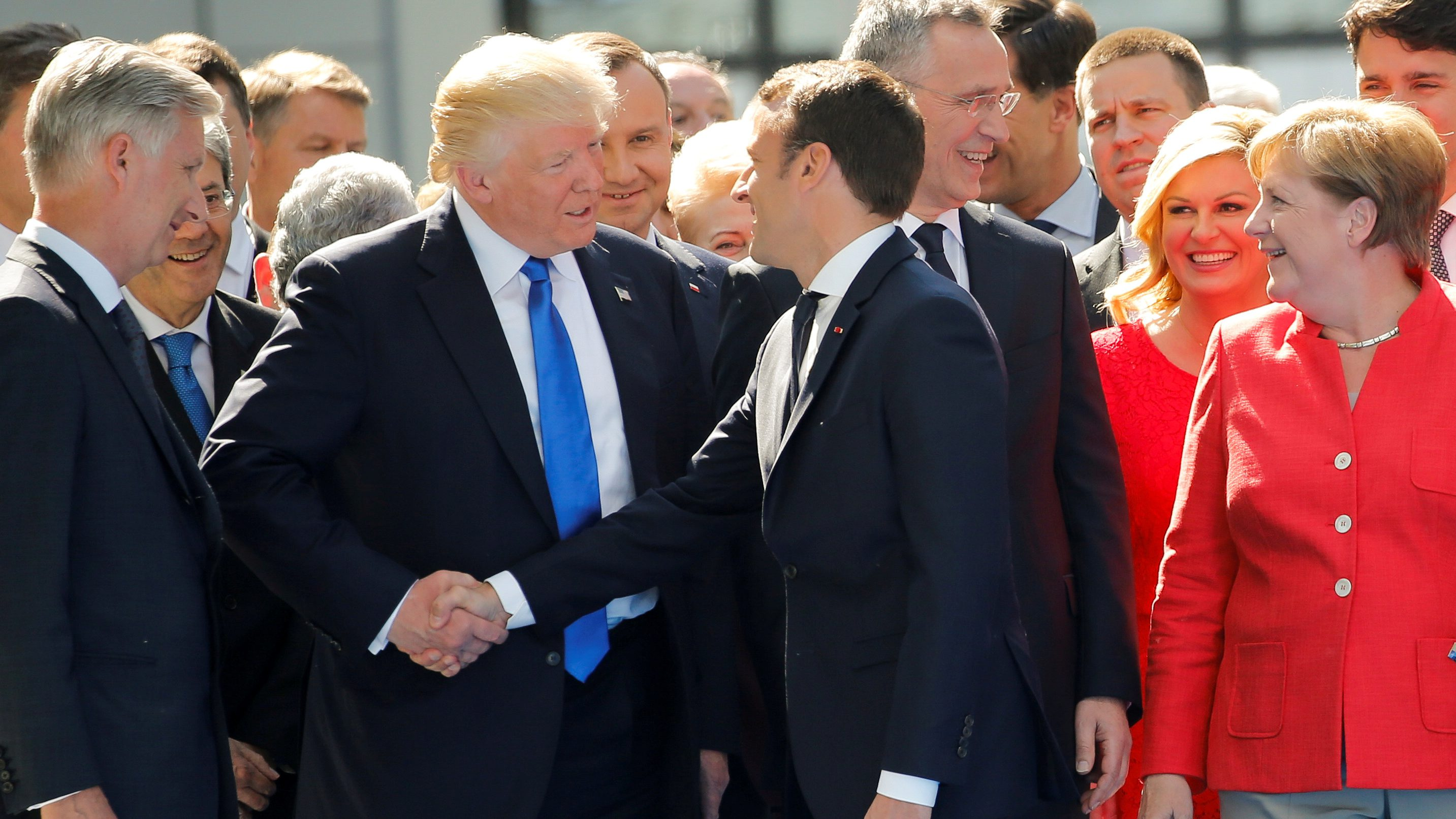 U.S. President Donald Trump jokes with French President Emmanuel Macron about their handshakes in front of NATO leaders, including German Chancellor Angela Merkel, NATO Secretary General Jens Stoltenberg (2ndR) and Belgium King Philippe (L), at the start of the NATO summit at their new headquarters in Brussels, Belgium, May 25, 2017. REUTERS/Jonathan Ernst     TPX IMAGES OF THE DAY - RTX37M45