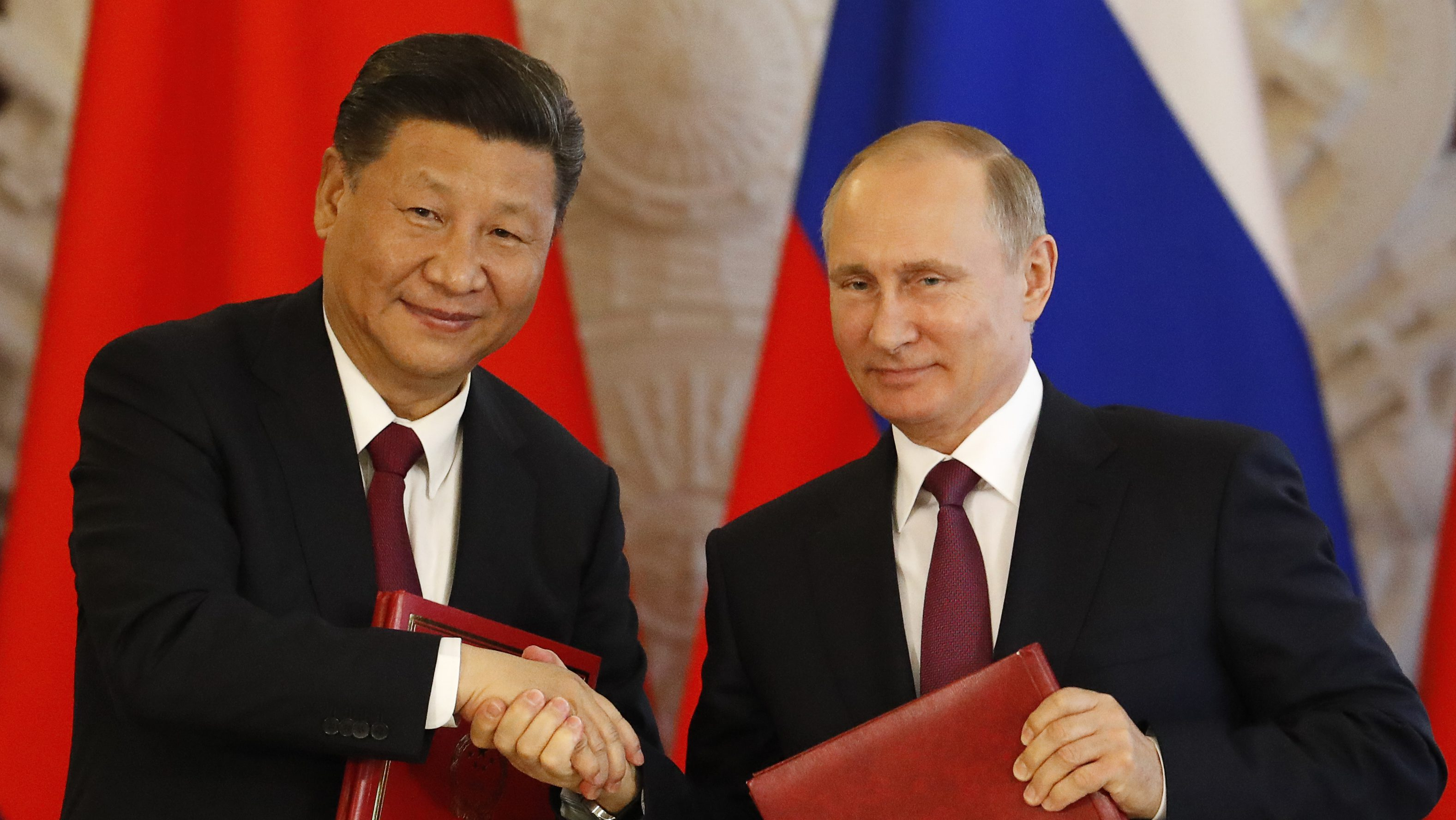 Russian President Vladimir Putin (R) shakes hands with his Chinese counterpart Xi Jinping during a signing ceremony following the talks at the Kremlin in Moscow, Russia July 4, 2017. REUTERS/Sergei Karpukhin - RTX39ZP2