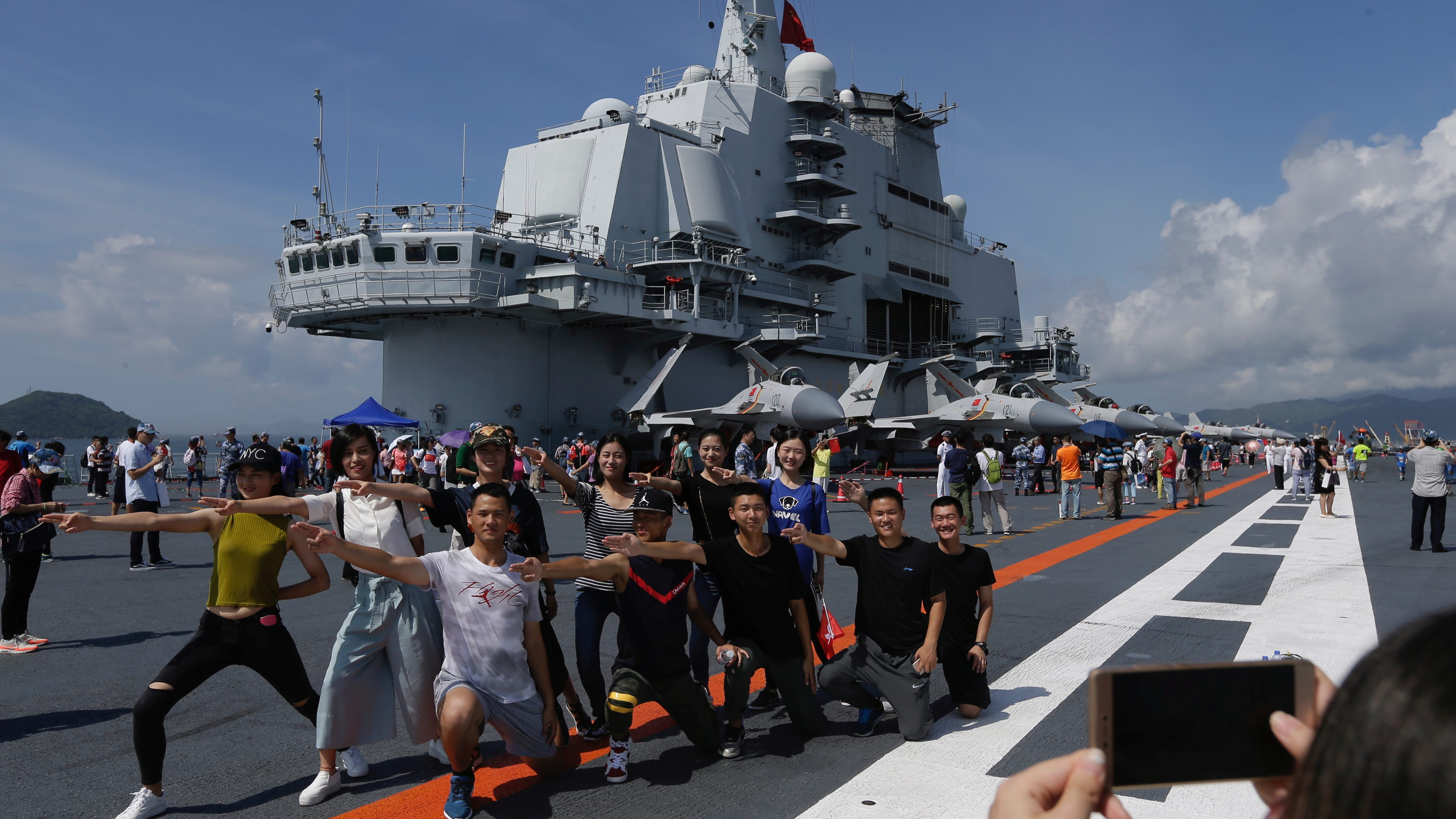 Visitors pose for pictures on China's first aircraft carrier Liaoning during an open day at a naval base in Hong Kong, China, July 9, 2017. Picture taken July 9, 2017.