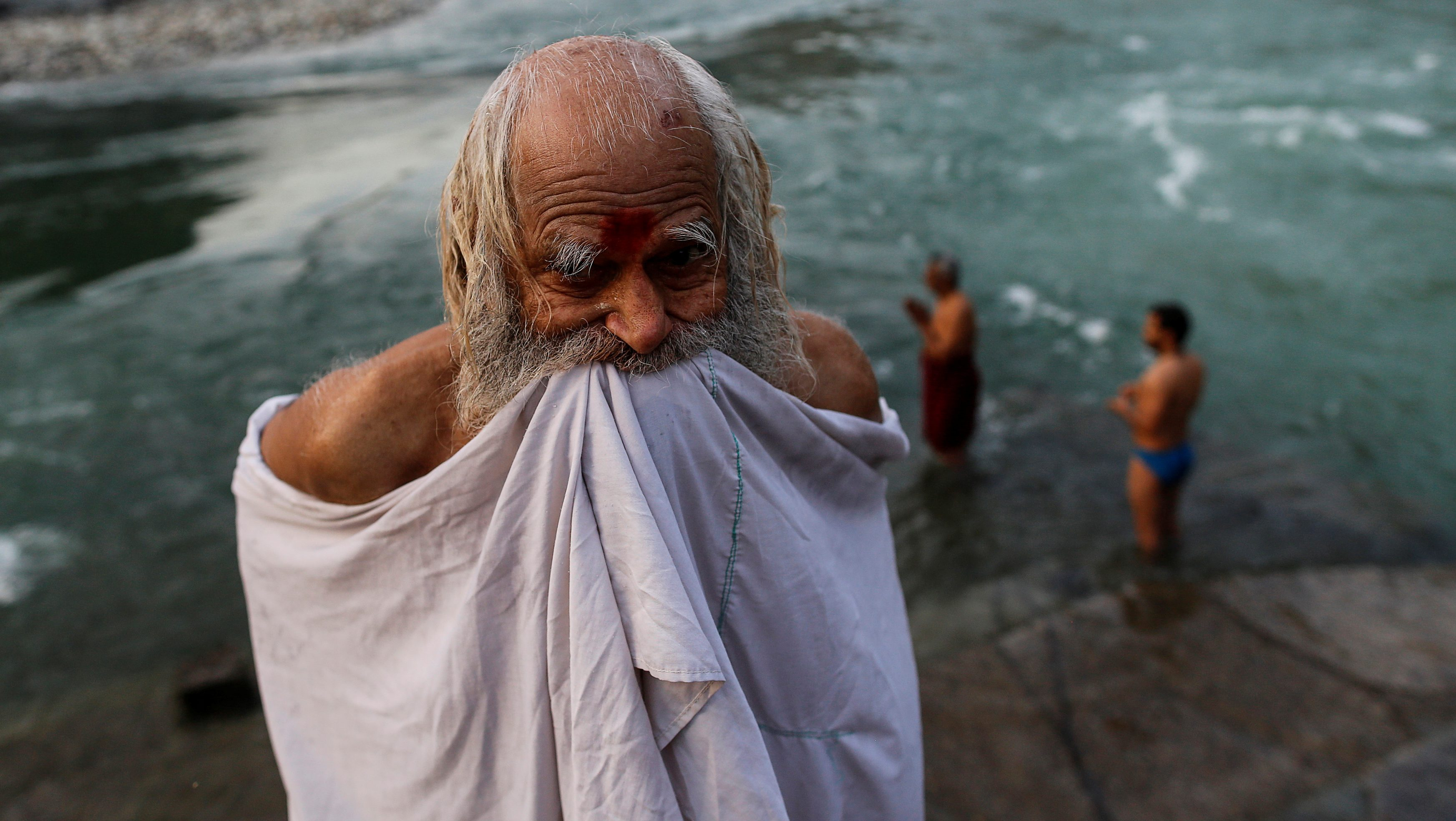 """A Hindu devotee holds up his clothes after taking a dip in the river Ganges in Devprayag, India, March 29, 2017. REUTERS/Danish Siddiqui  SEARCH """"SIDDIQUI GANGES"""" FOR THIS STORY. SEARCH """"WIDER IMAGE"""" FOR ALL STORIES. - RTX3ASE2"""
