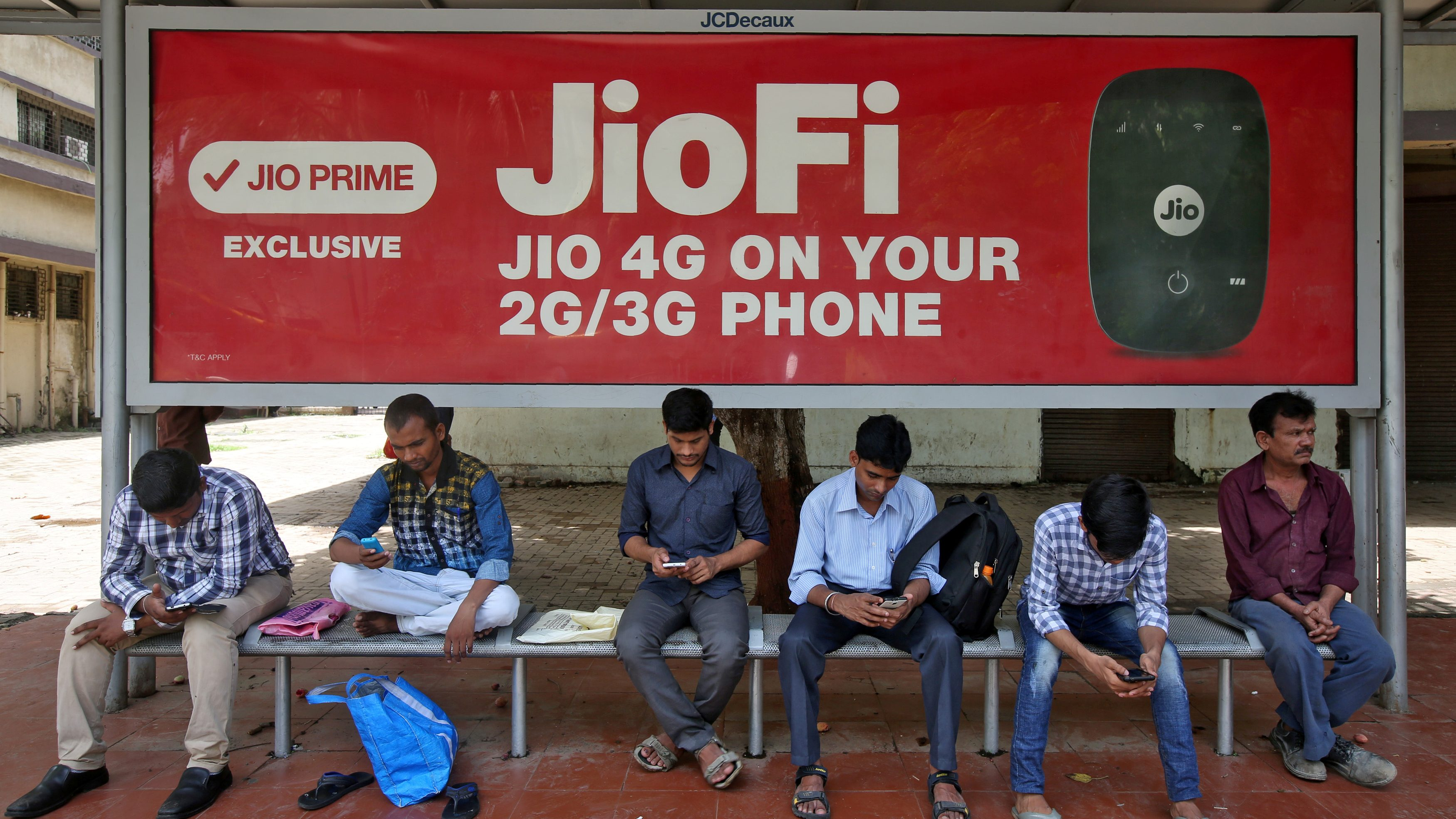 Commuters use their mobile phones as they wait at a bus stop with an advertisement of Reliance Industries' Jio telecoms unit, in Mumbai, India July 10, 2017. REUTERS/Shailesh Andrade - RTX3ASPA