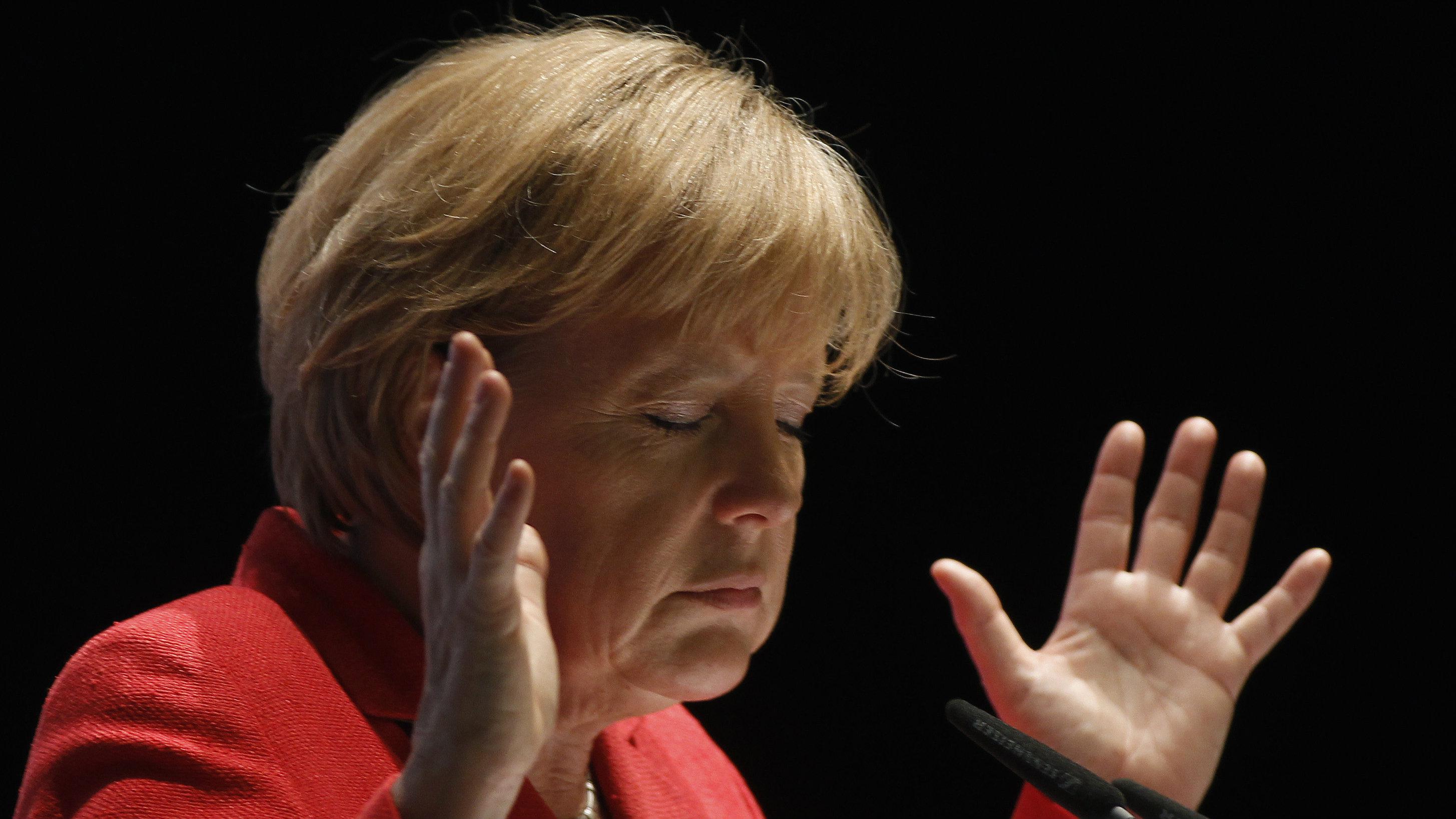 Angela Merkel closes her eyes and raises her hands