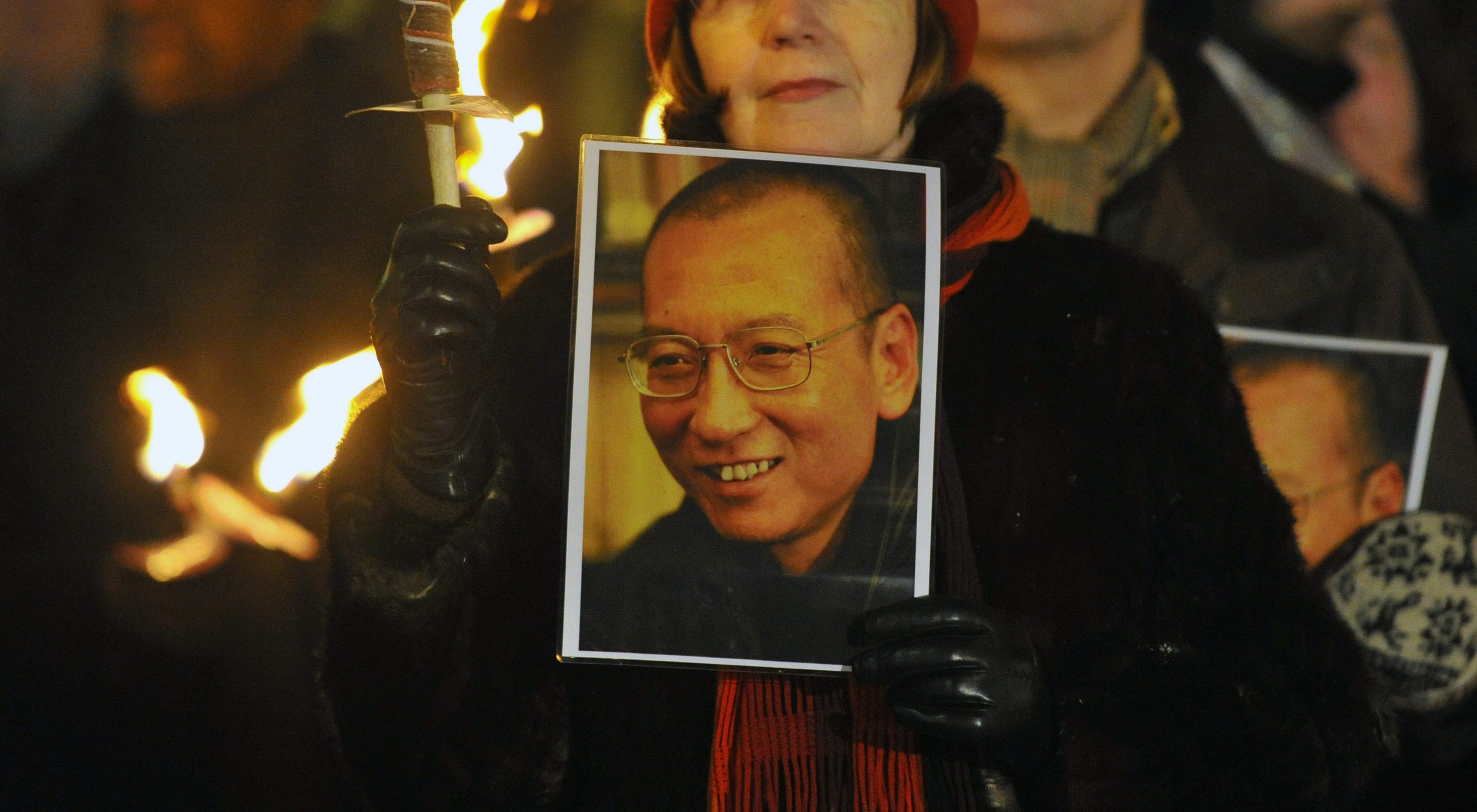 A woman holds a photograph of Liu Xiaobo during a torchlit procession in the centre of Oslo following the Nobel Peace Prize ceremony in December 10, 2010.