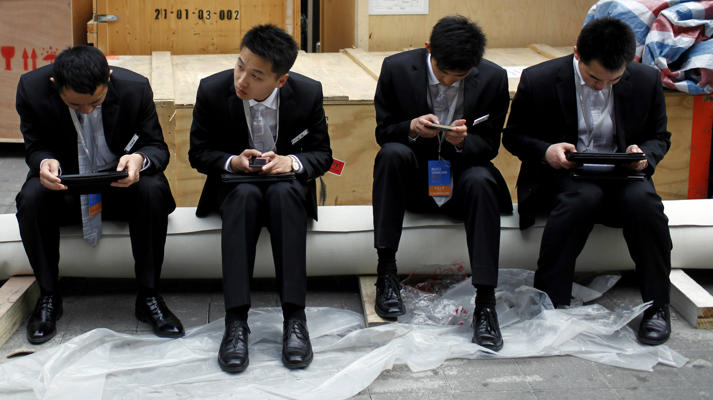 A row of people looking at their smartphones and tablets
