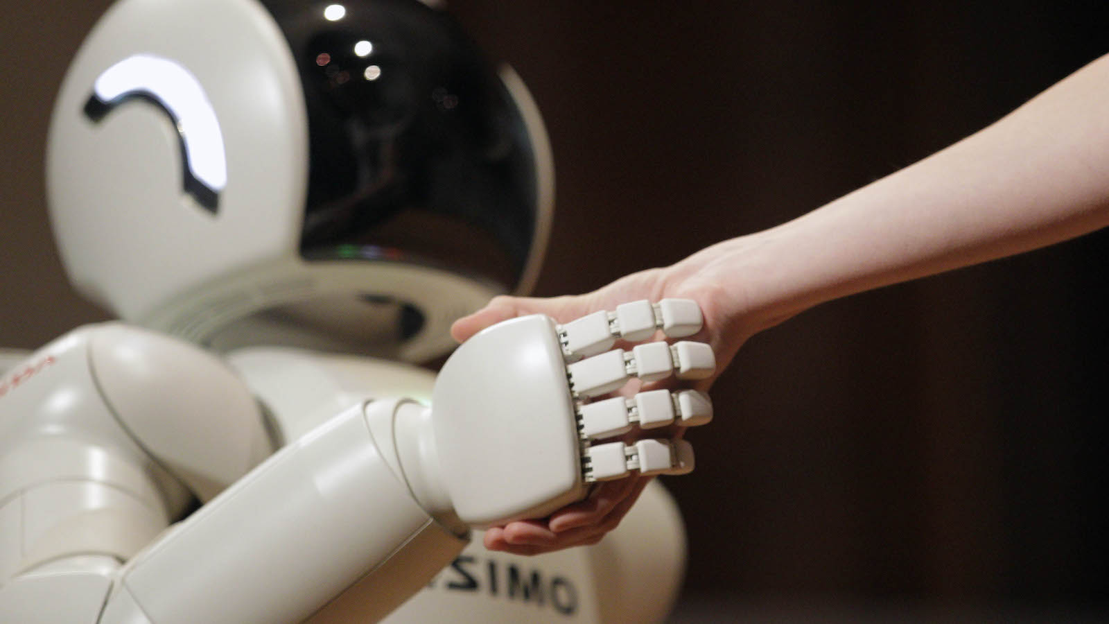 Honda Motors' humanoid robot ASIMO (Advanced Step in Innovative Mobility) shakes hands with assistant as it demonstrates its skills, in Belgrade, Serbia, Monday, Sept. 24, 2012. (AP Photo/Darko Vojinovic)