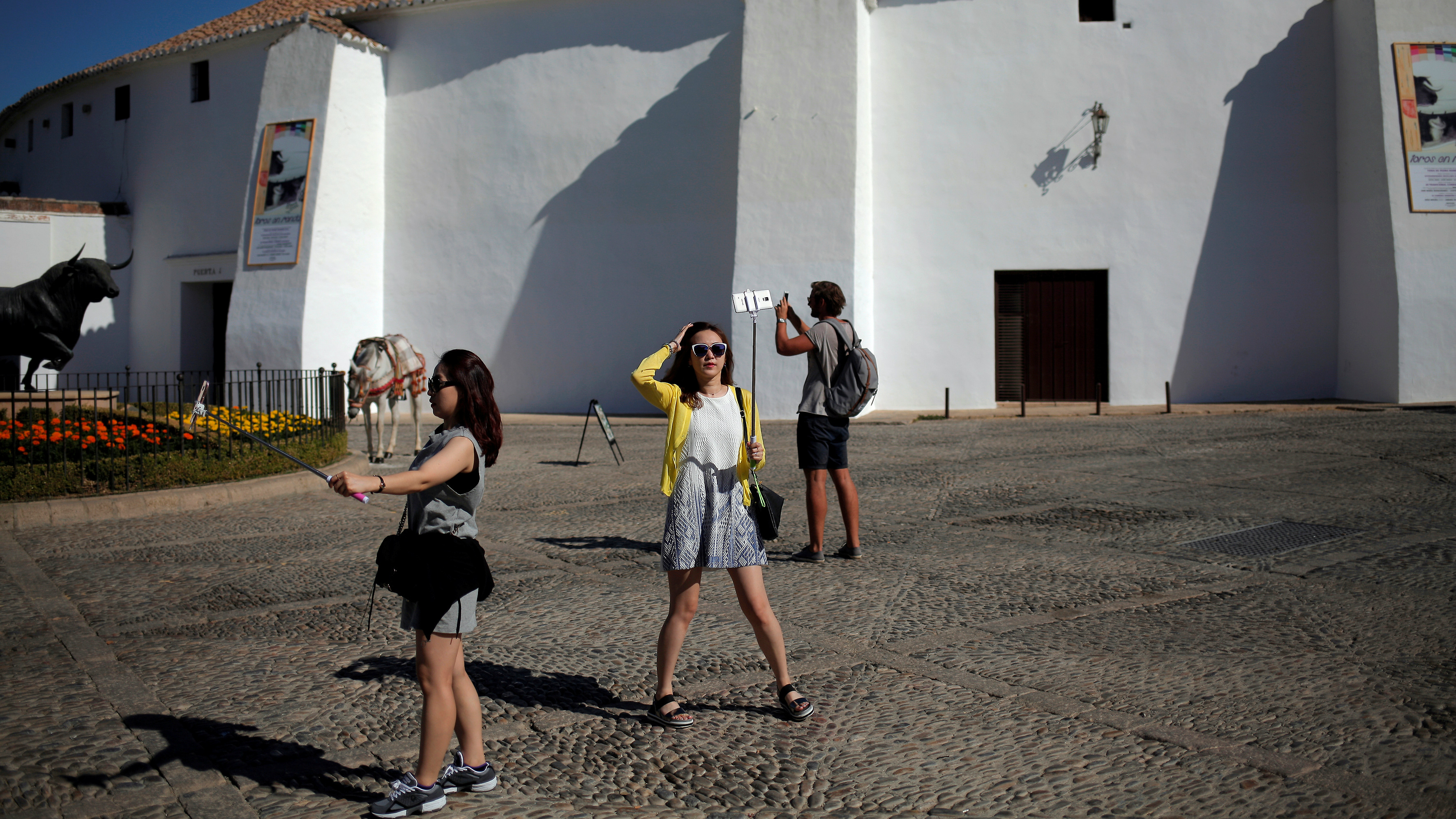 Tourists use selfie sticks to take photographs next to the statue of a bull.