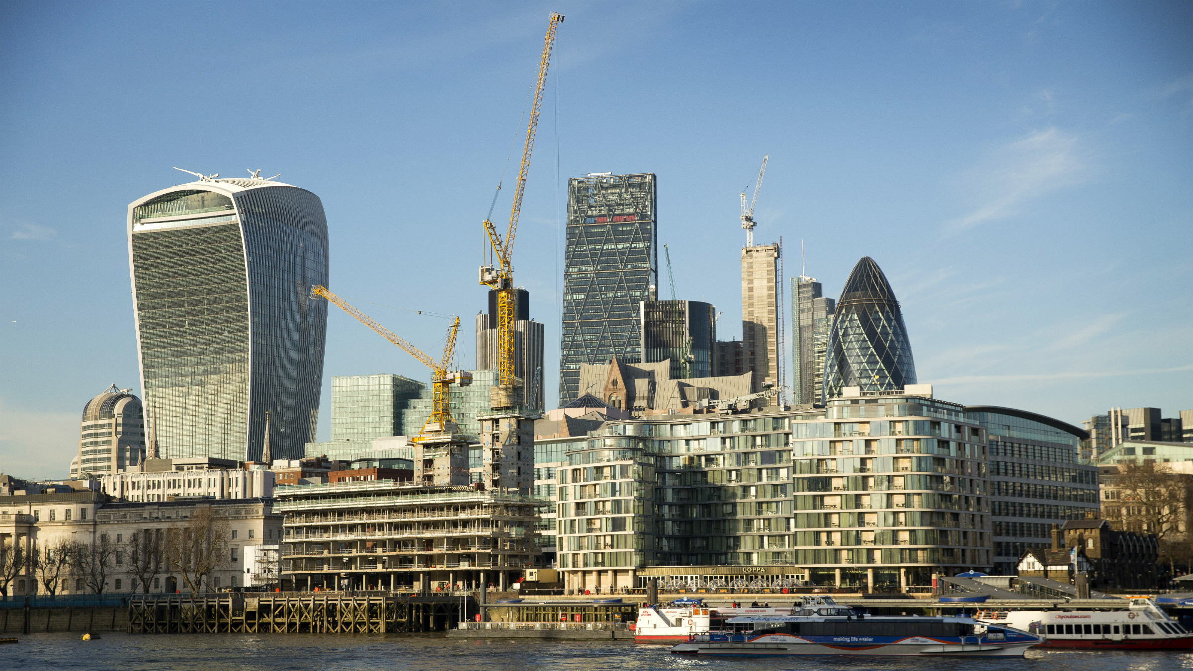 A general view of cranes on the London skyline alongside 20 Fenchurch, left, known locally as the Walkie-Talkie and the fifth tallest completed building in the City of London, as seen from the river Thames, Thursday, Jan. 19, 2017.