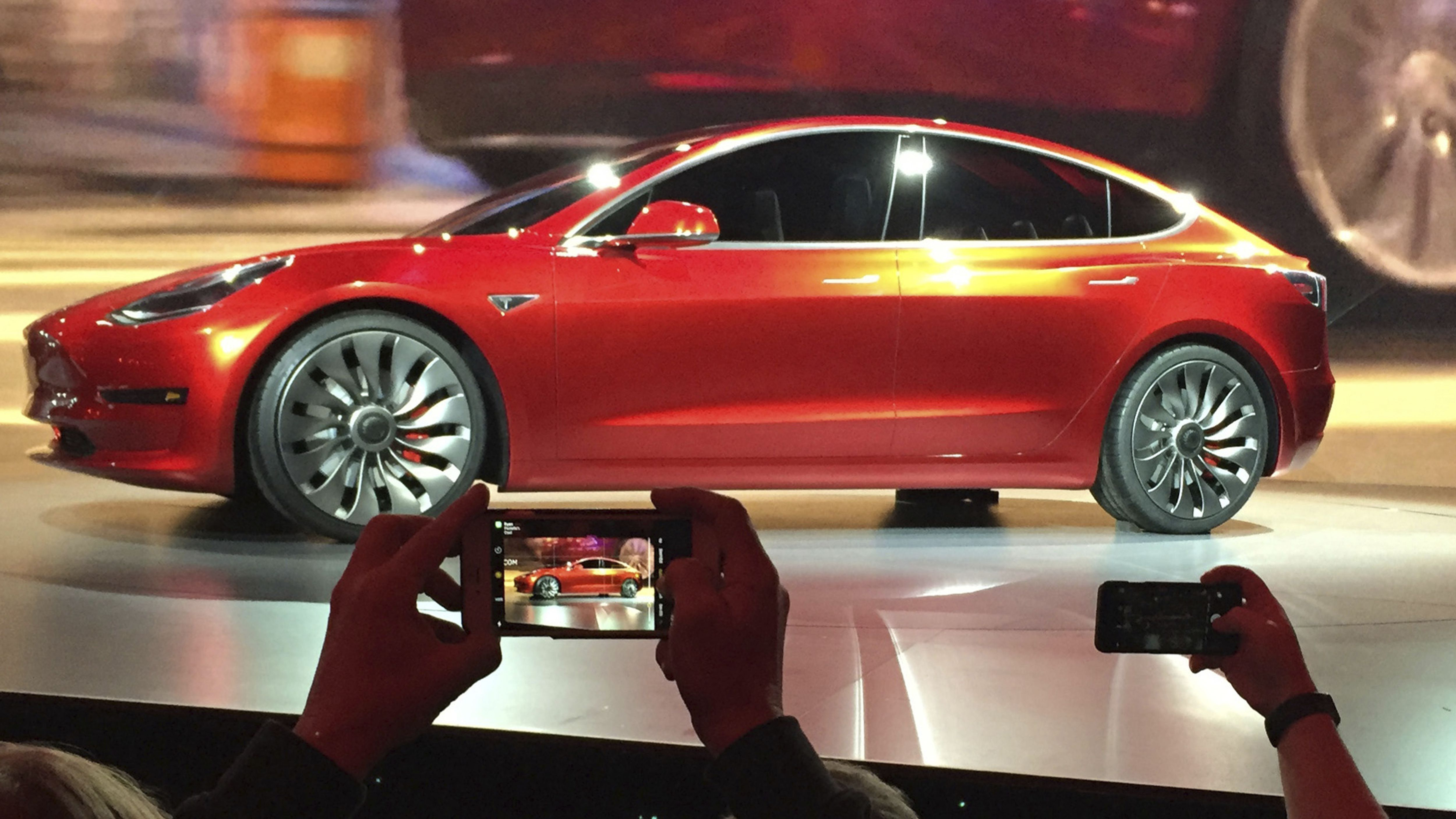 In this March 31, 2016, file photo, Tesla Motors unveils the new lower-priced Model 3 sedan at the Tesla Motors design studio in Hawthorne, Calif. Electric car maker Tesla said on Monday, July 3, 2017, that its Model 3 car will go on sale on Friday.