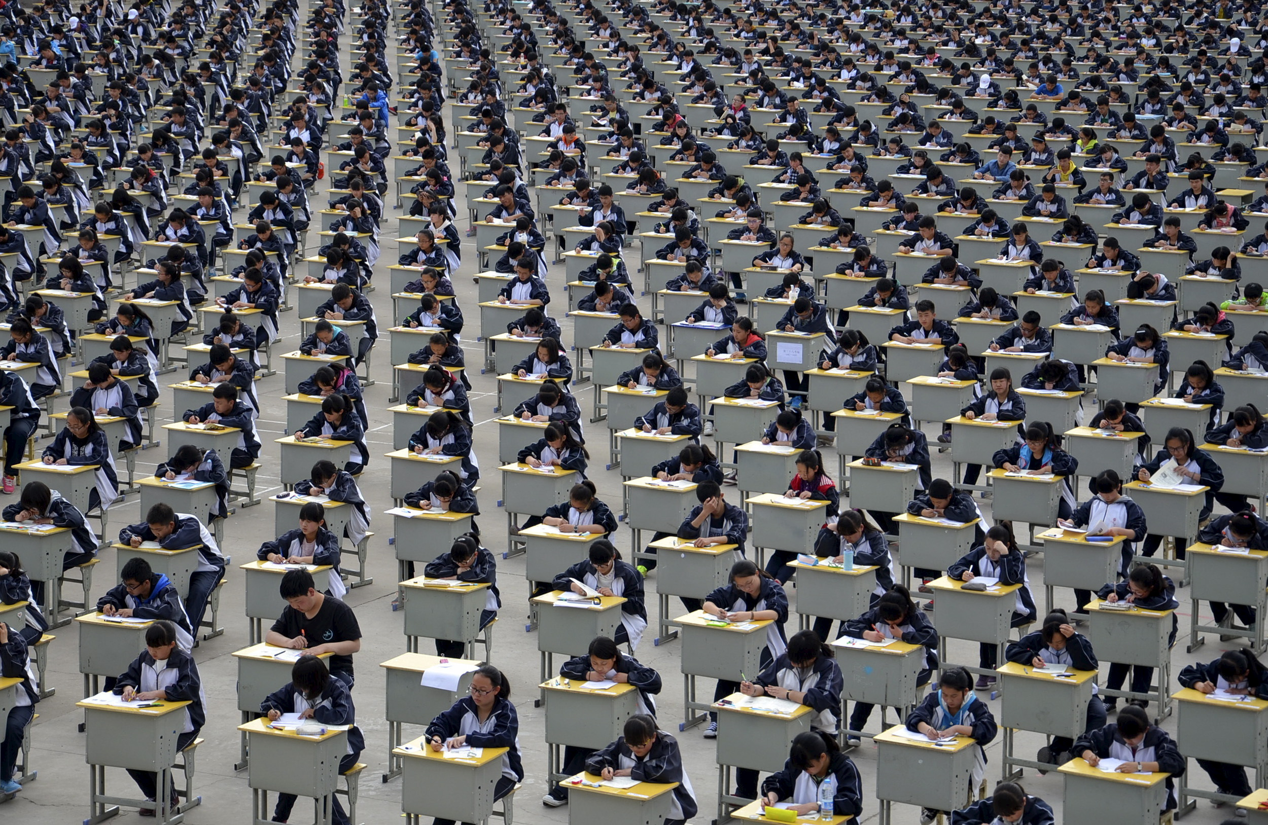 Students take an examination on an open-air playground at a high school in Yichuan, Shaanxi province April 11, 2015. More than 1,700 freshmen students took part in the exam on Saturday, which was the first attempt by the school to take it in open-air. The school said the reasons was due to the insufficient indoor space and also that it could be a test of the students' organizing capacity, local media reported.