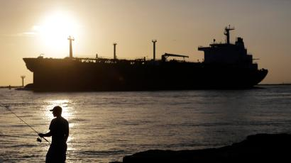 FILE - In this July 21, 2015, file photo, an oil tanker passes a fisherman as it enters a channel near Port Aransas, Texas, heading for the Port of Corpus Christi. The U.S., seemingly awash in crude oil after an energy boom sent thousands of workers scurrying to the plains of Texas and North Dakota, will begin exporting oil for the first time since the 1973 oil embargo.