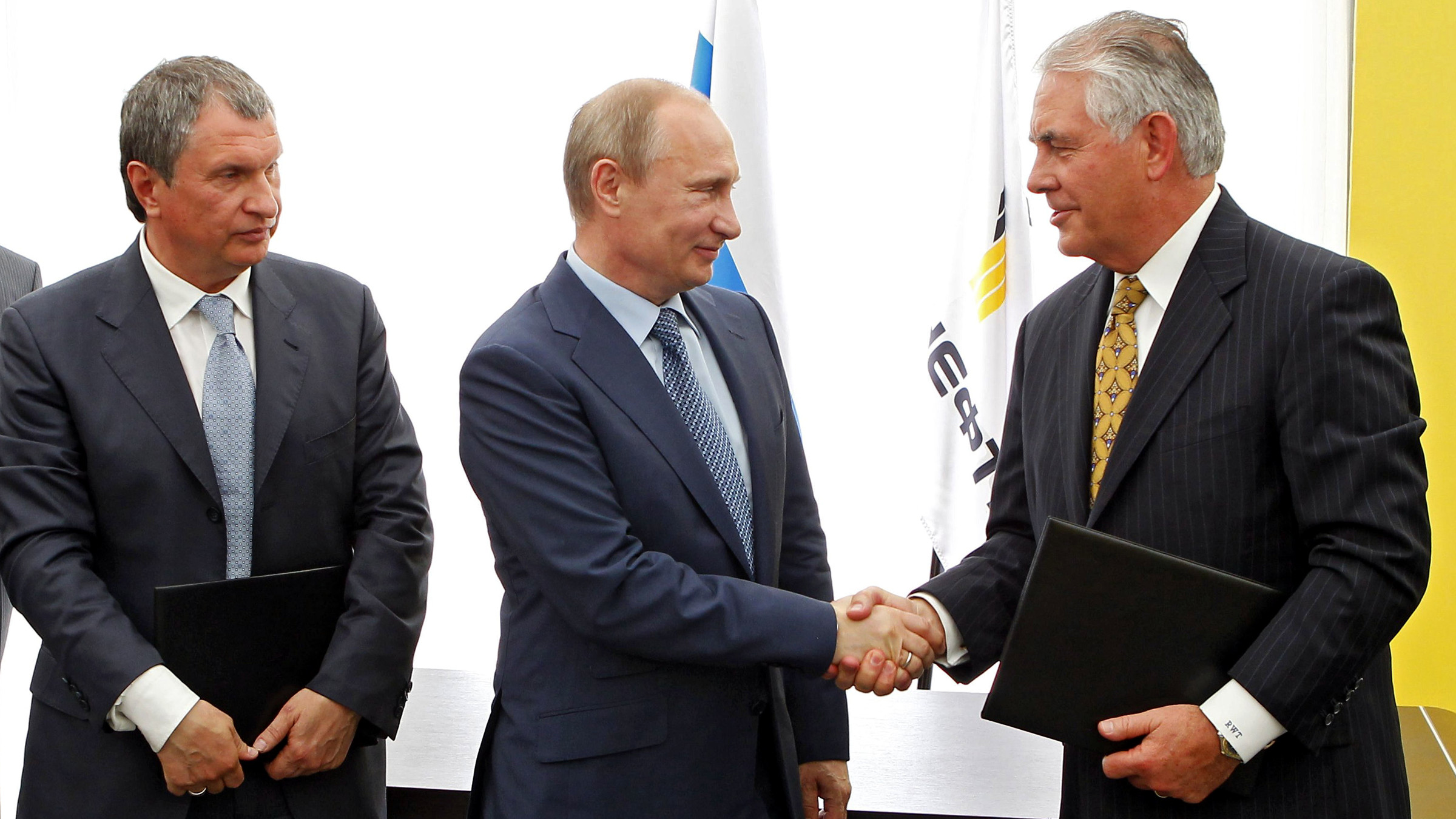Russian President Vladimir Putin, center, and Exxon Mobil Corp. CEO Rex Tillerson shake hands at a signing ceremony of an agreement between state-controlled Russian oil company Rosneft and Exxon Mobil corporation at the Black Sea port of Tuapse, southern Russia, Friday, June 15, 2012. At left is CEO of state-controlled Russian oil company Rosneft Igor Sechin