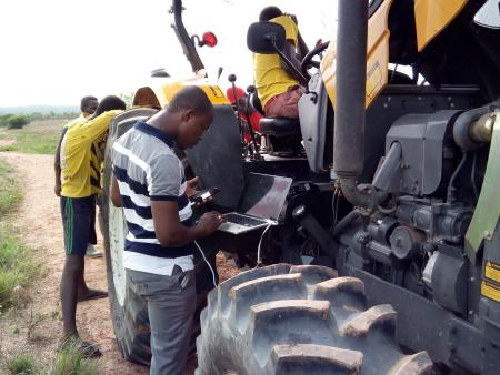 A tractor operator helps a farmer with a request made through the Trotro Tractor service, where farmers dial a code to book a tractor to plow their land.