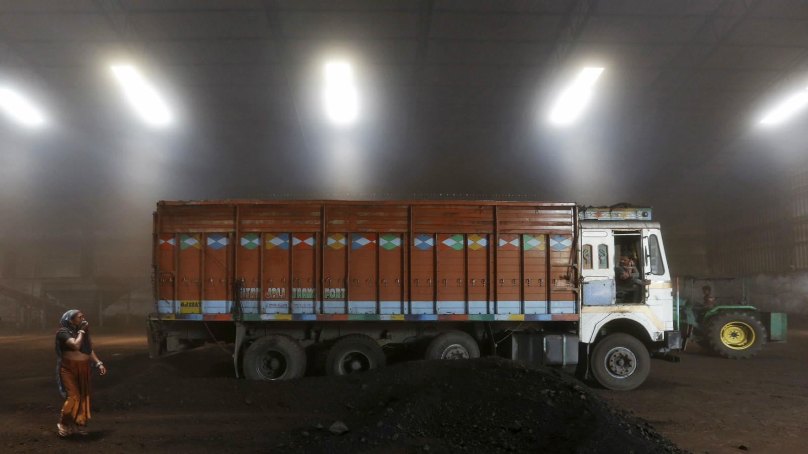 A worker speaks with the driver after unloading coal from a supply truck at a yard on the outskirts of the western Indian city of Ahmedabad April 15, 2015. Fewer power cuts are likely in India this summer after a surge in output at Coal India helped generators amass record stocks, a turnaround for Narendra Modi who had to battle a power crisis within months of becoming prime minister last May. Fast-track mine approvals, tighter production oversight and more flexibility in coal sales have helped power station stocks recover from a six-year low hit in October, vindicating Modi's pitch to voters as the state leader who brought round-the-clock power to industrial Gujarat.