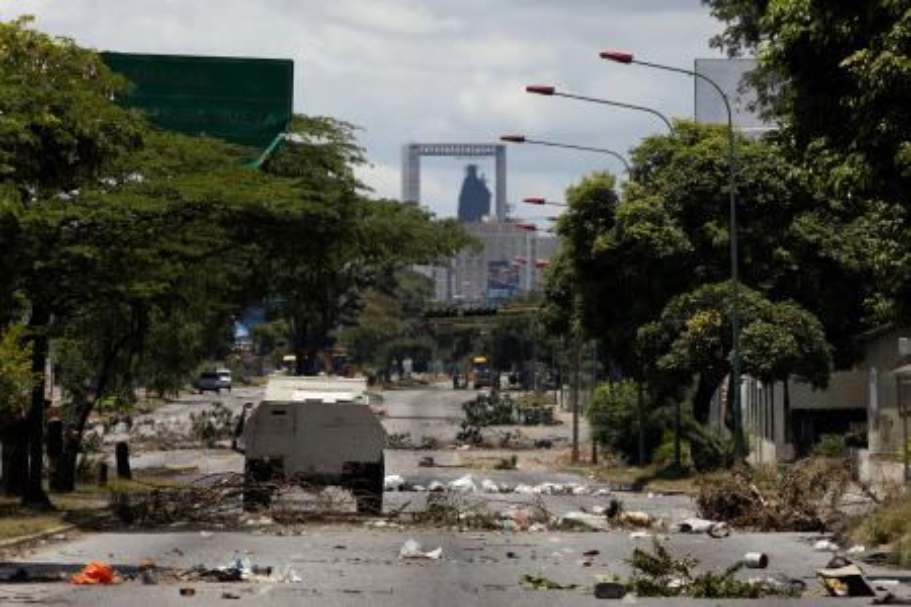 A Bolivarian National Guard vehicle drives down a barren street during a clash between opposition protesters and the Bolivarian National Guard