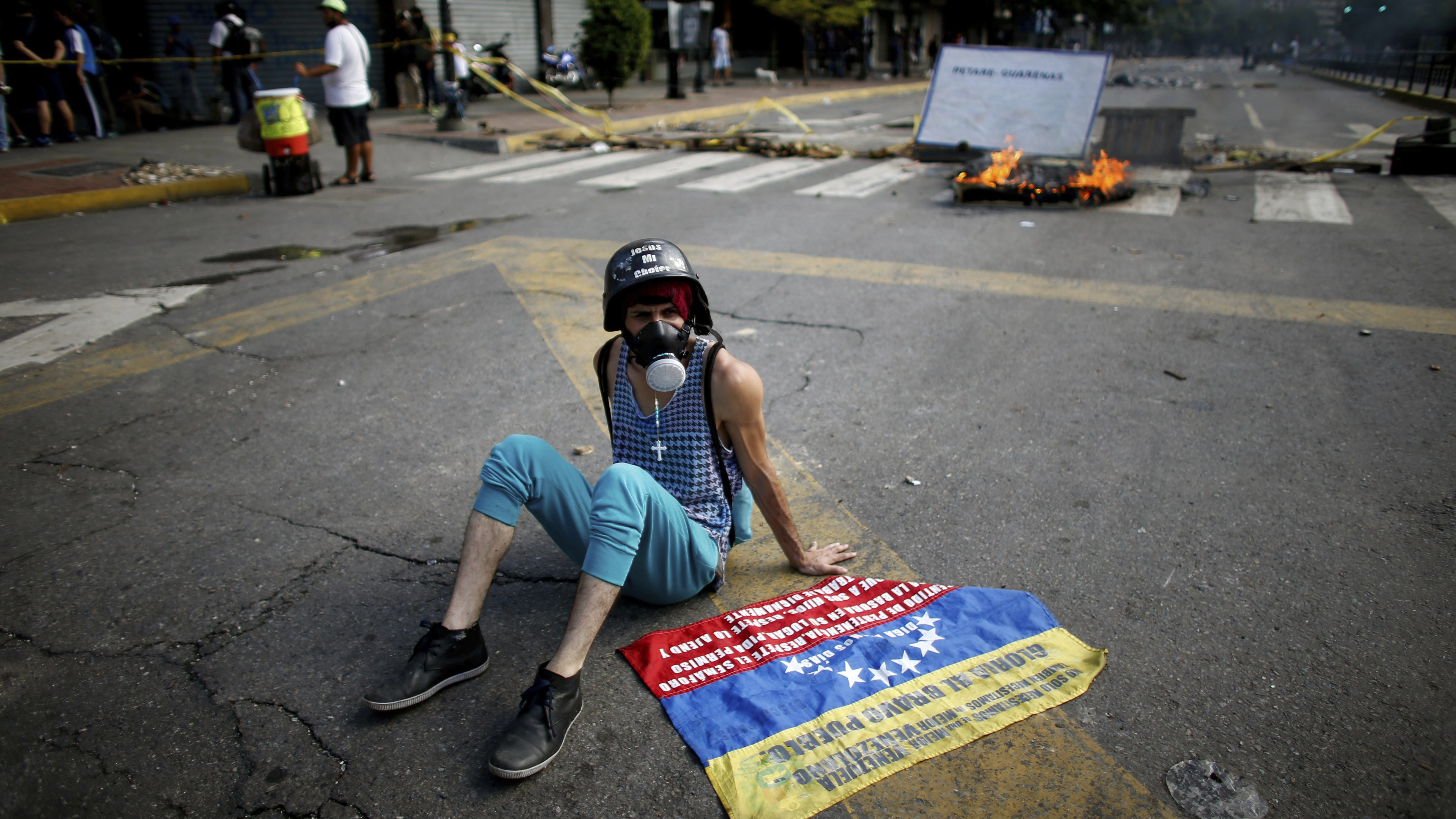 An anti-government demonstrator rests on the ground near a barricade in Caracas, Venezuela