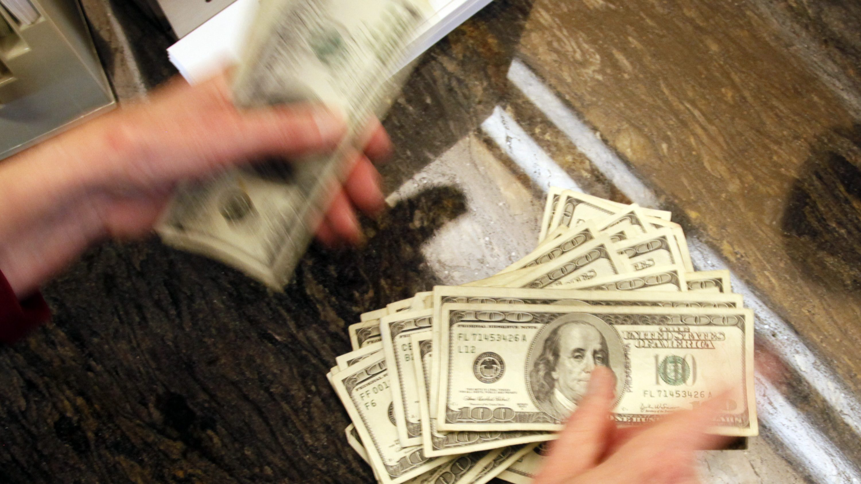 Four thousand U.S. dollars are counted out by a banker counting currency at a bank in Westminster, Colorado November 3, 2009.