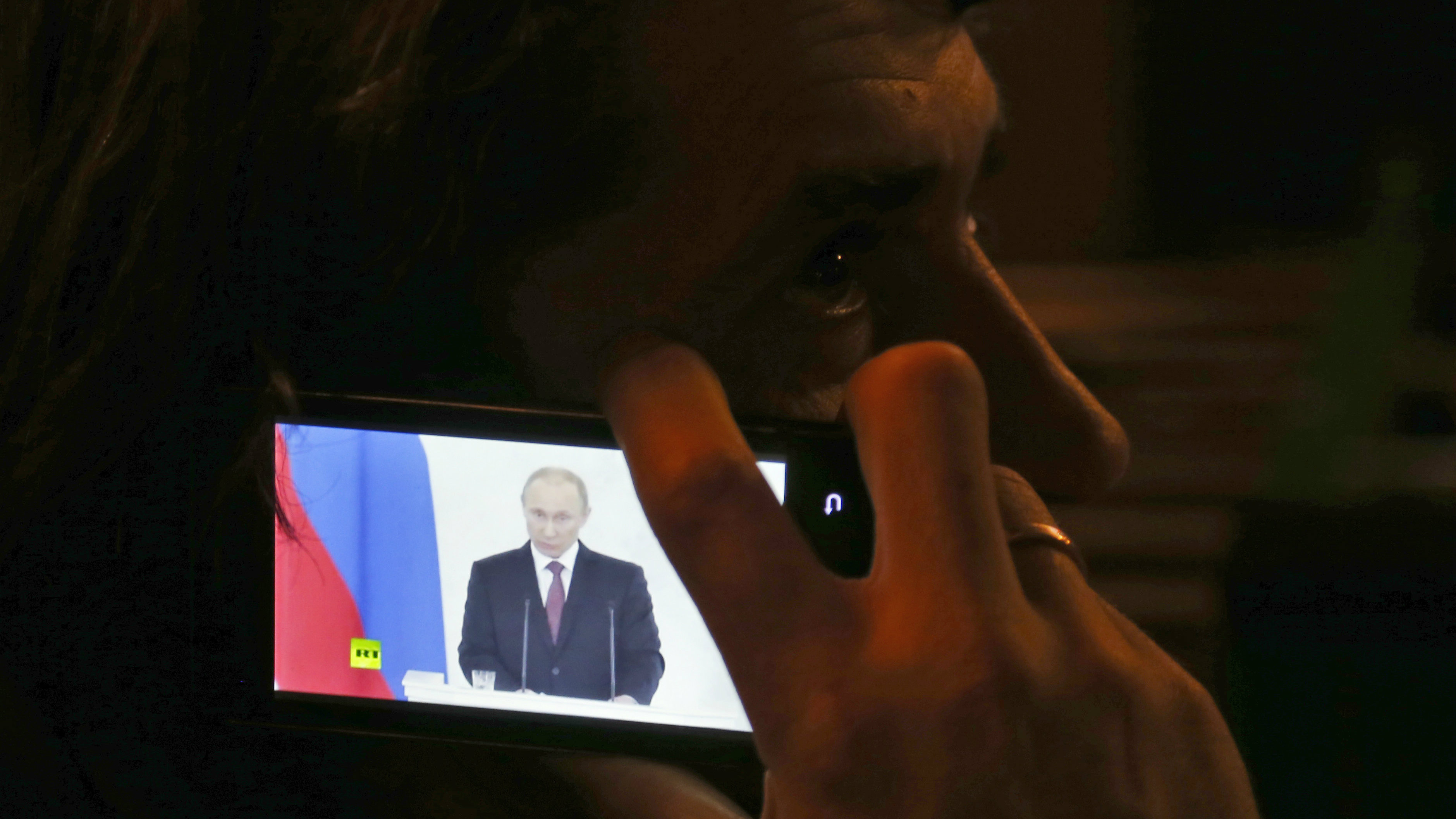 "A patron listens to Russian President Vladimir Putin deliver a statement with a mobile phone in a bar in Donetsk, Ukraine, Tuesday, March 18, 2014. Putin on Tuesday fiercely defended Russia's move to annex Crimea saying Crimea's vote on Sunday to join Russia was in line with ""democratic norms and international law."""