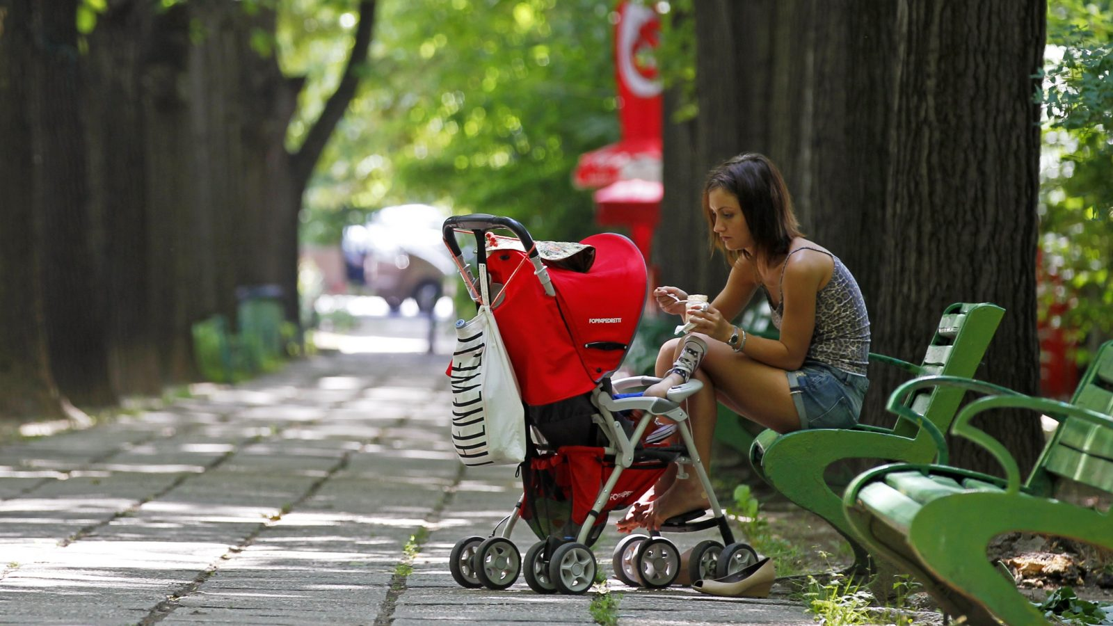 A woman feeds her child in a park in Bucharest June 7, 2013.   REUTERS/Bogdan Cristel (ROMANIA - Tags: SOCIETY) - RTX10F26
