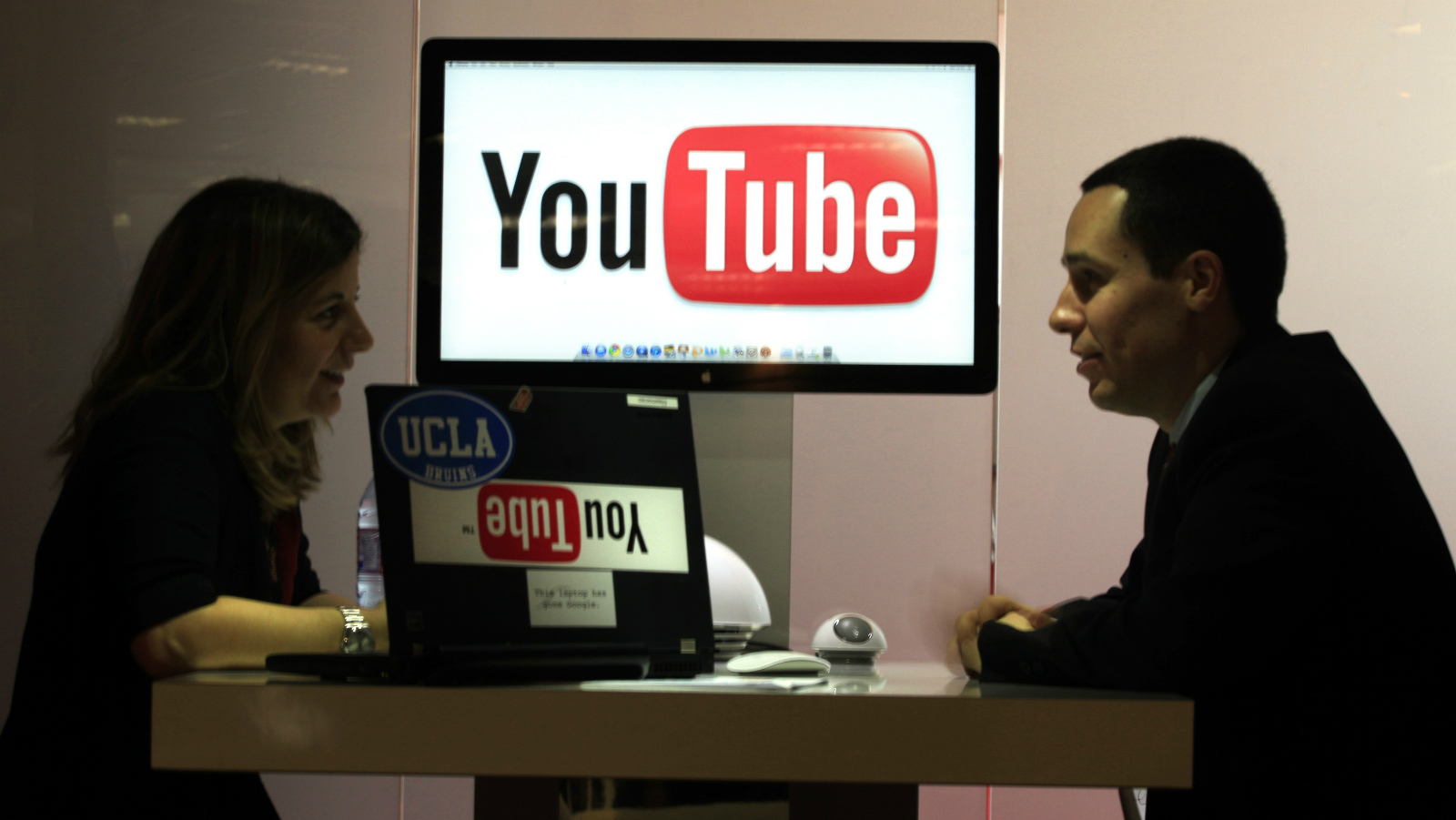 """Visitors are seen at """"You Tube"""" stand during the MIDEM, which is the international record music publishing and video music market, in Cannes January 23, 2011."""