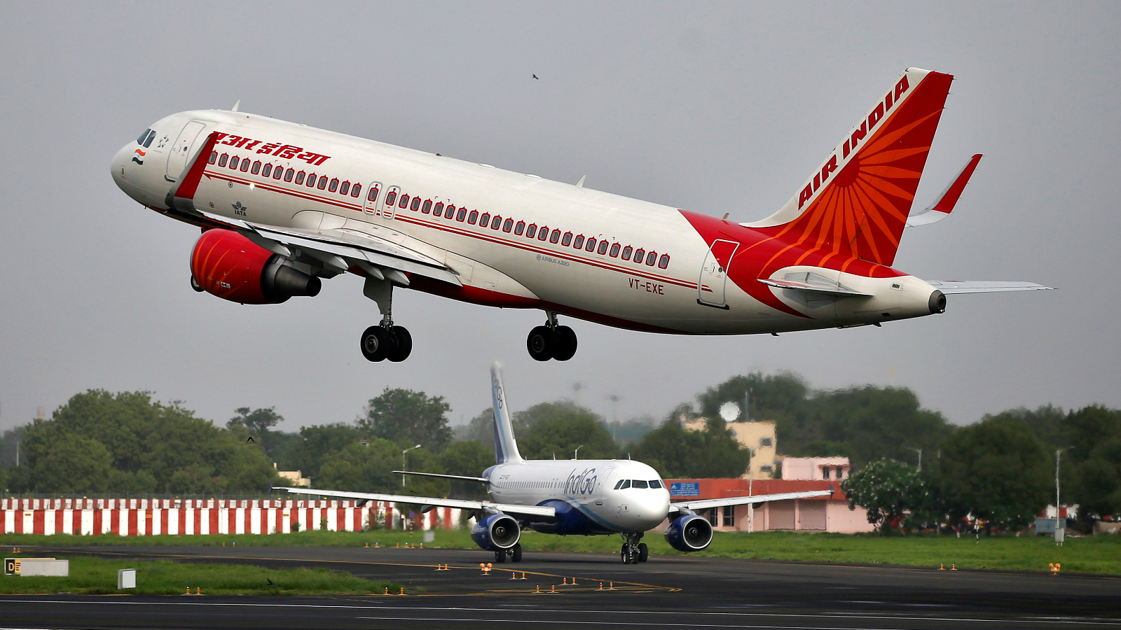An Air India aircraft takes off as an IndiGo Airlines aircraft waits for clearance at the Sardar Vallabhbhai Patel International Airport in Ahmedabad, India, July 7, 2017. Picture taken July 7, 2017. To match Analysis AIR INDIA-PRIVATISATION/