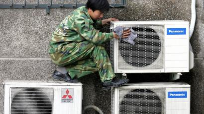 Man cleaning air conditioning units.