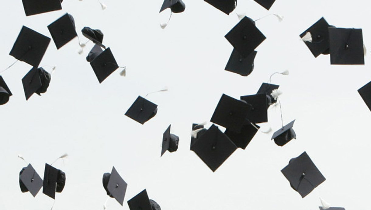 Graduation hats thrown into the air.