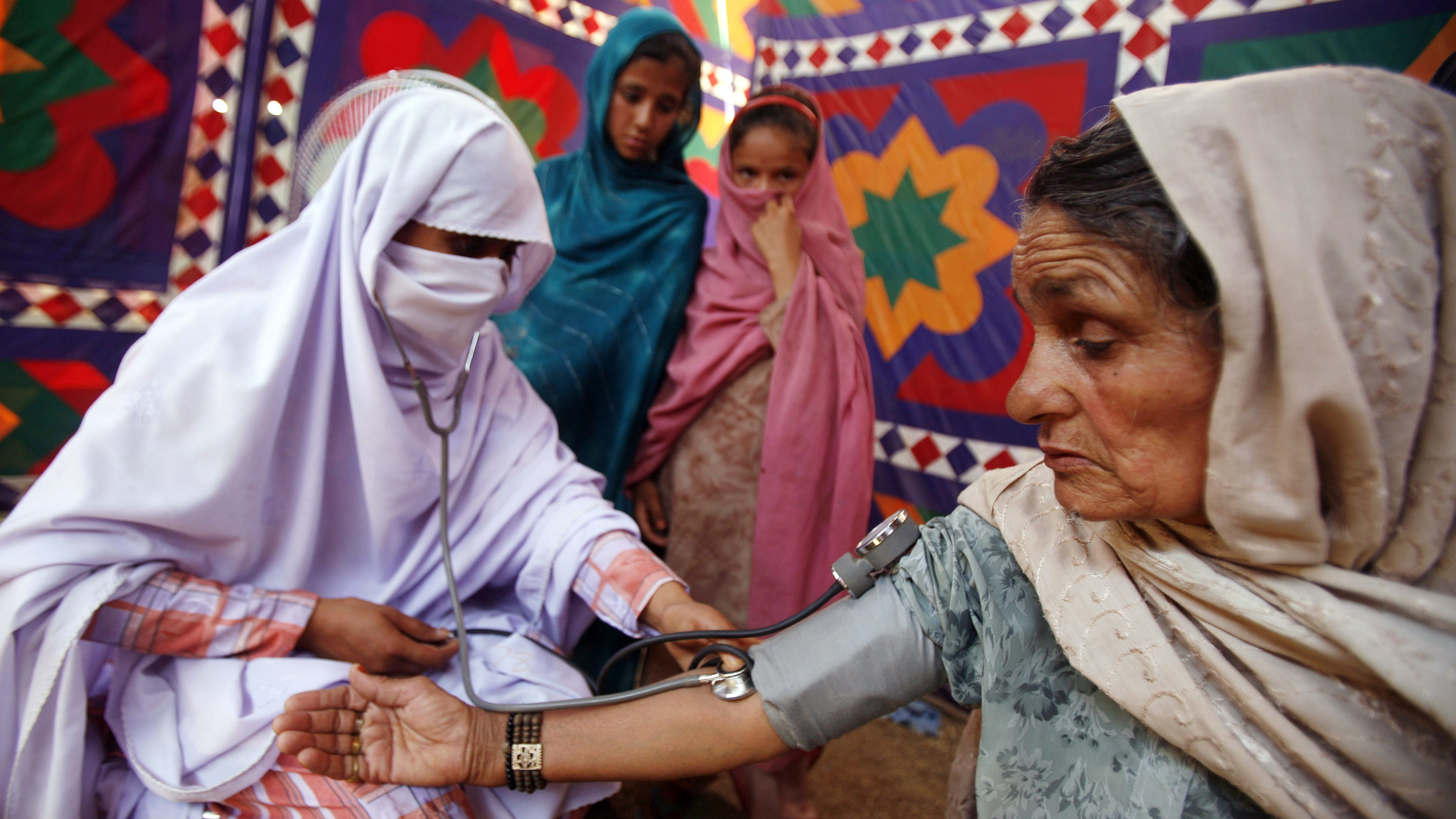 A doctor, left, treats a woman at a medical clinic in a tent at the Sheikh Yasin refugee camp at Mardan, in northwest Pakistan, Monday, May 18, 2009.  More than a million Pakistanis have fled fighting between the army and Taliban militants in the Swat Valley, with around 100,000 living in camps near the town of Mardan, south of the battle zone. (AP Photo/Greg Baker)